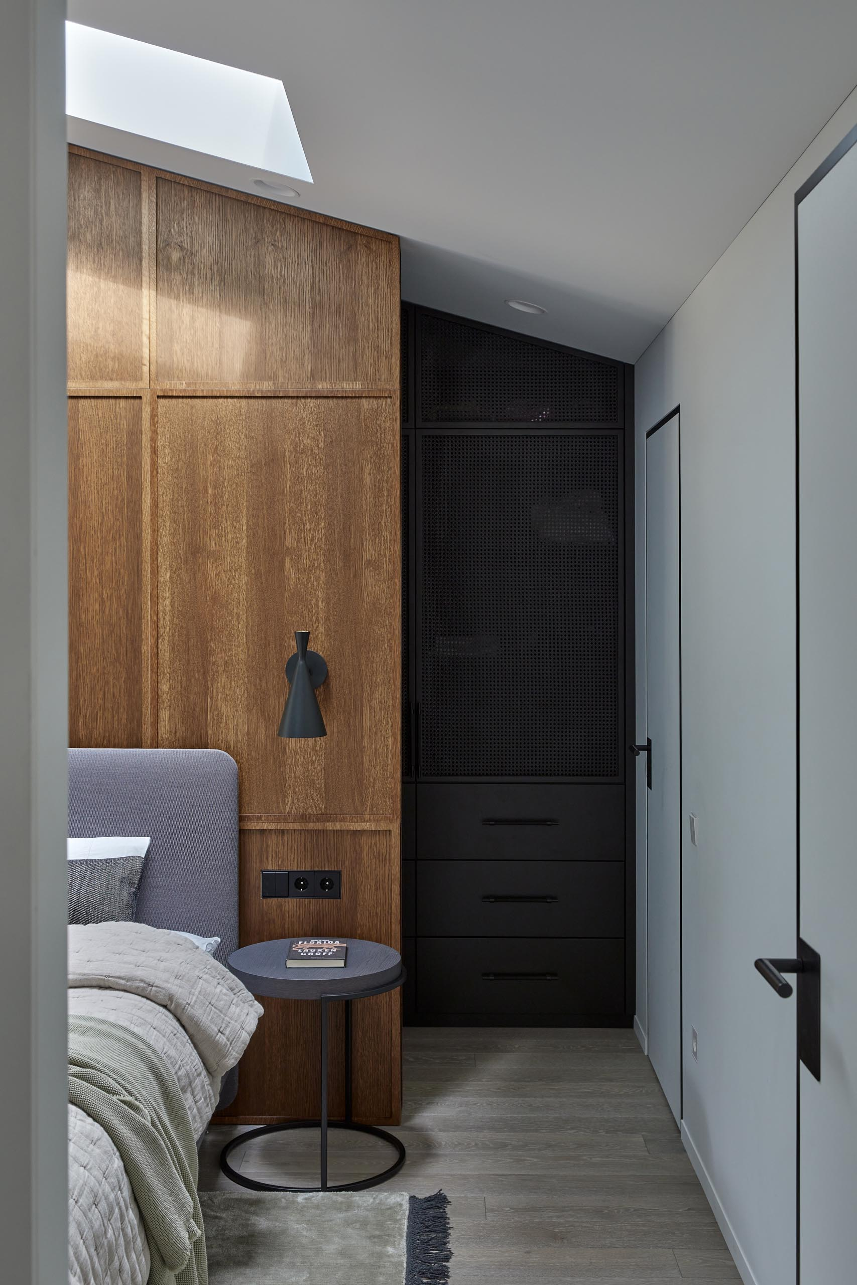In is modern primary bedroom, there's yet another wood accent wall, this time, providing a backdrop for the gray upholstered bed, while the dark cabinetry of the wardrobe provides a contrasting element in the room.