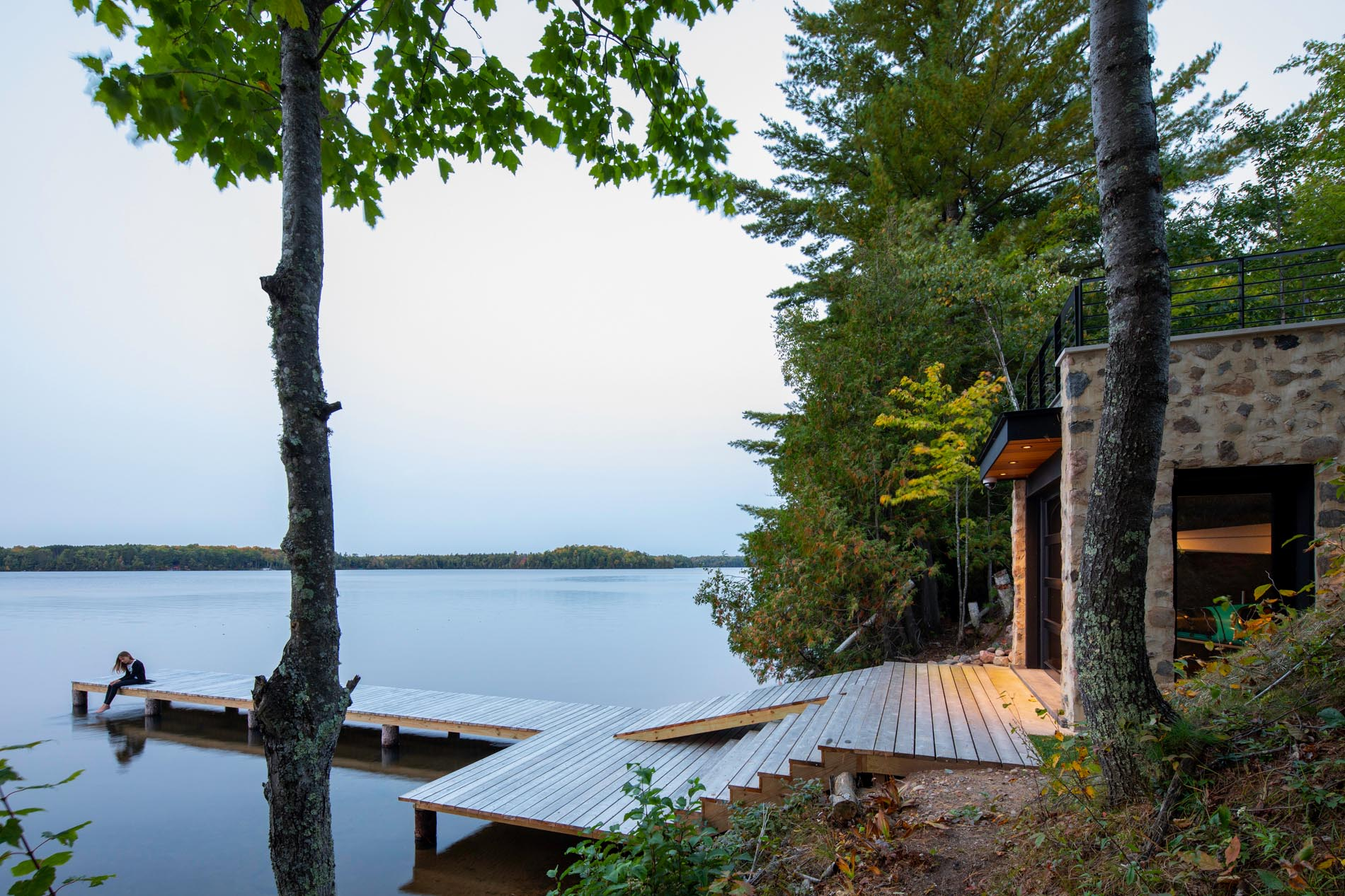 This modern home includes steps that lead down to a boathouse with a rooftop deck, as well as a dock.