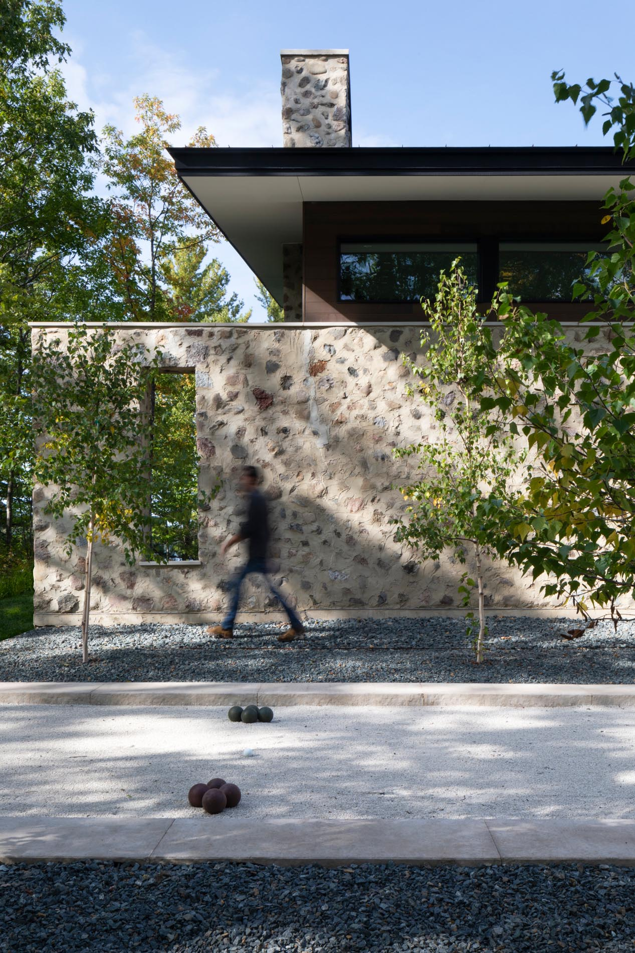 A modern home with stone walls and a bocce court.