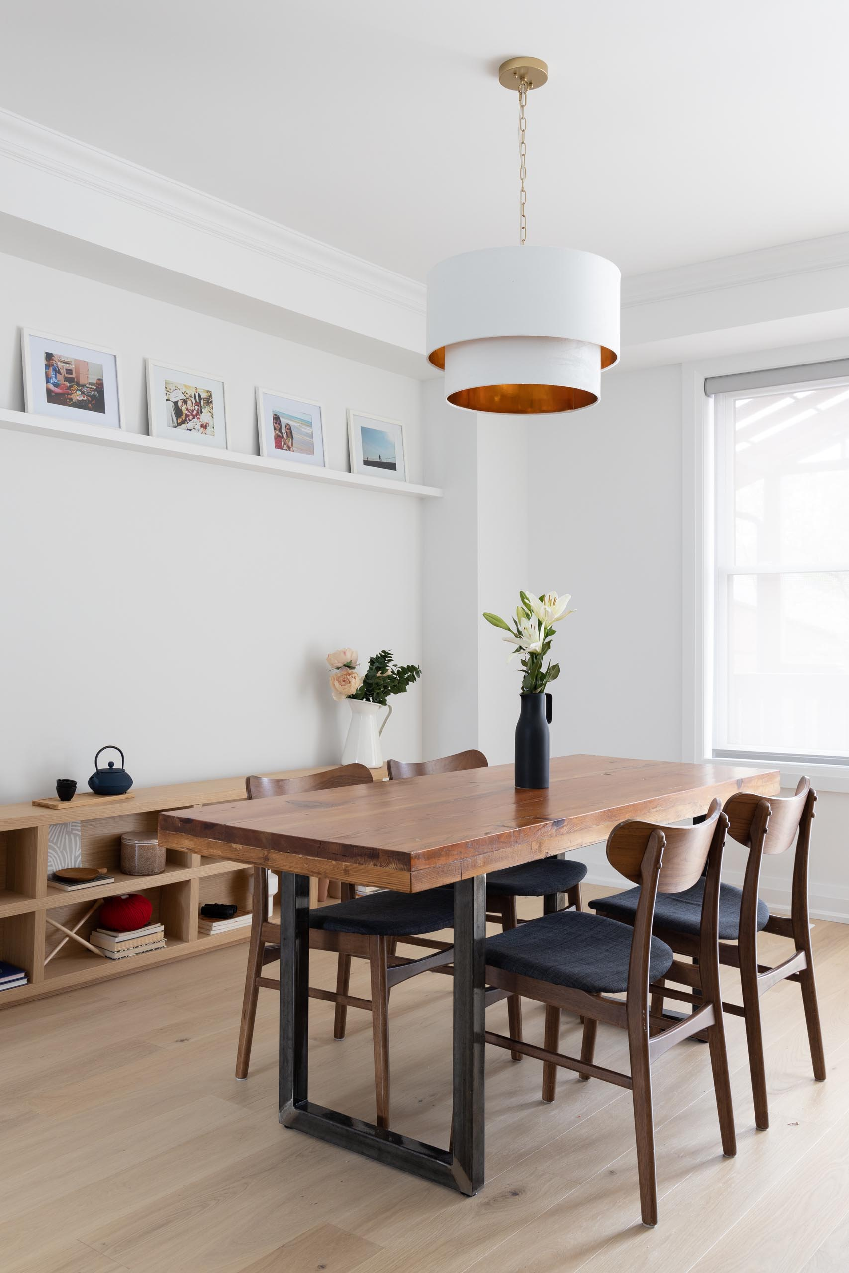 In this modern dining room, there's a wood table with a steel base that's located underneath a white pendant light with a metallic interior. A low wood console lines the wall, while a floating white shelf acts as a picture rail for family photos.