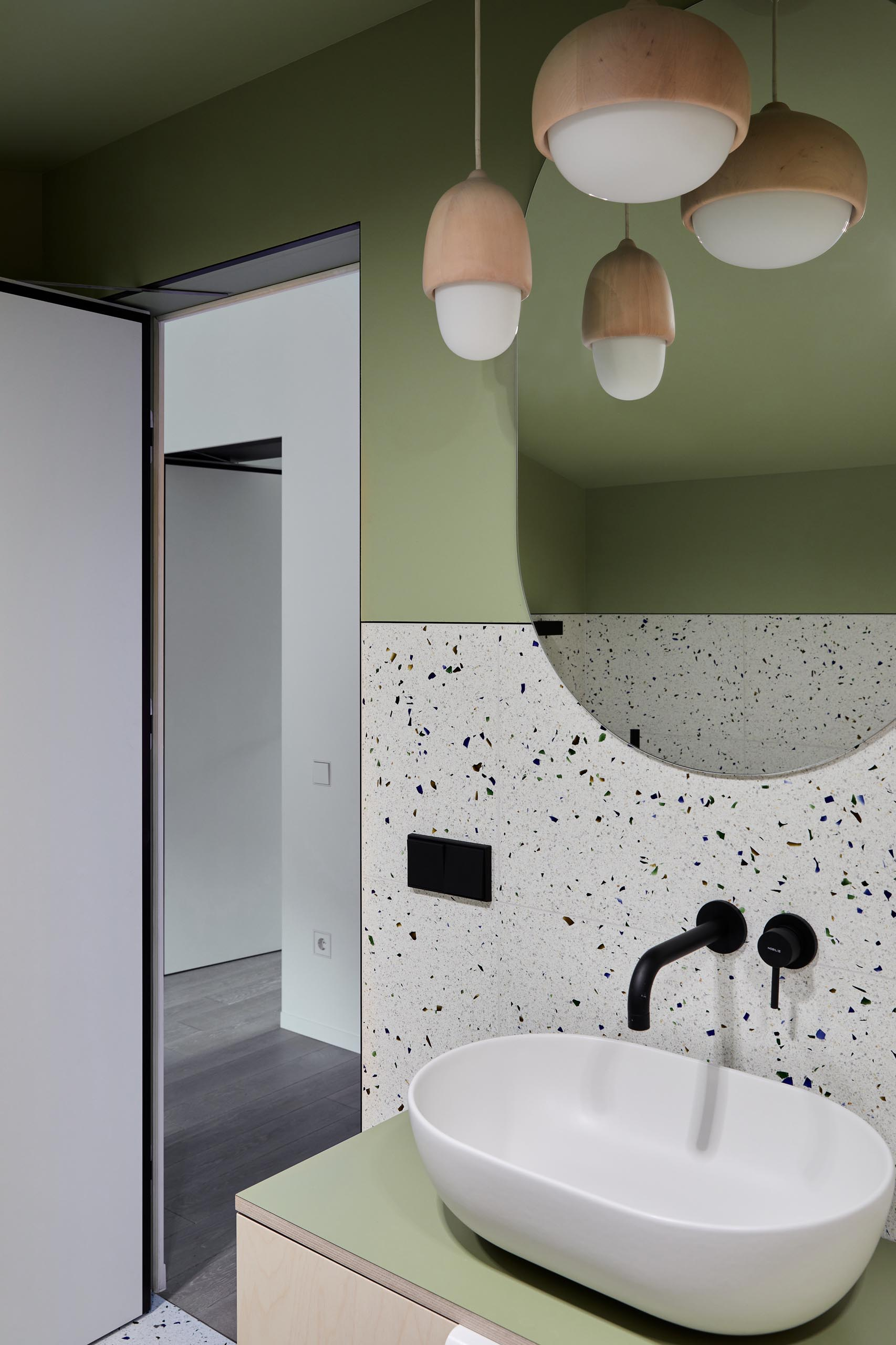 In this modern bathroom, matte green walls have been combined with terrazzo and wood pendant lights.