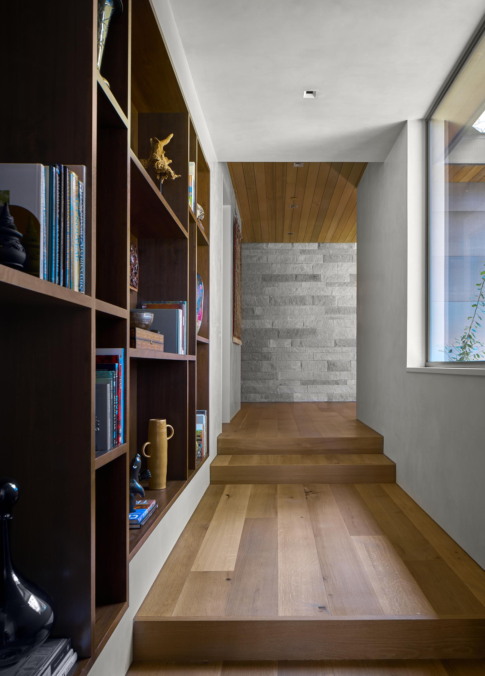 A hallway with wood flooring and built-in shelving connects the various areas of the home.