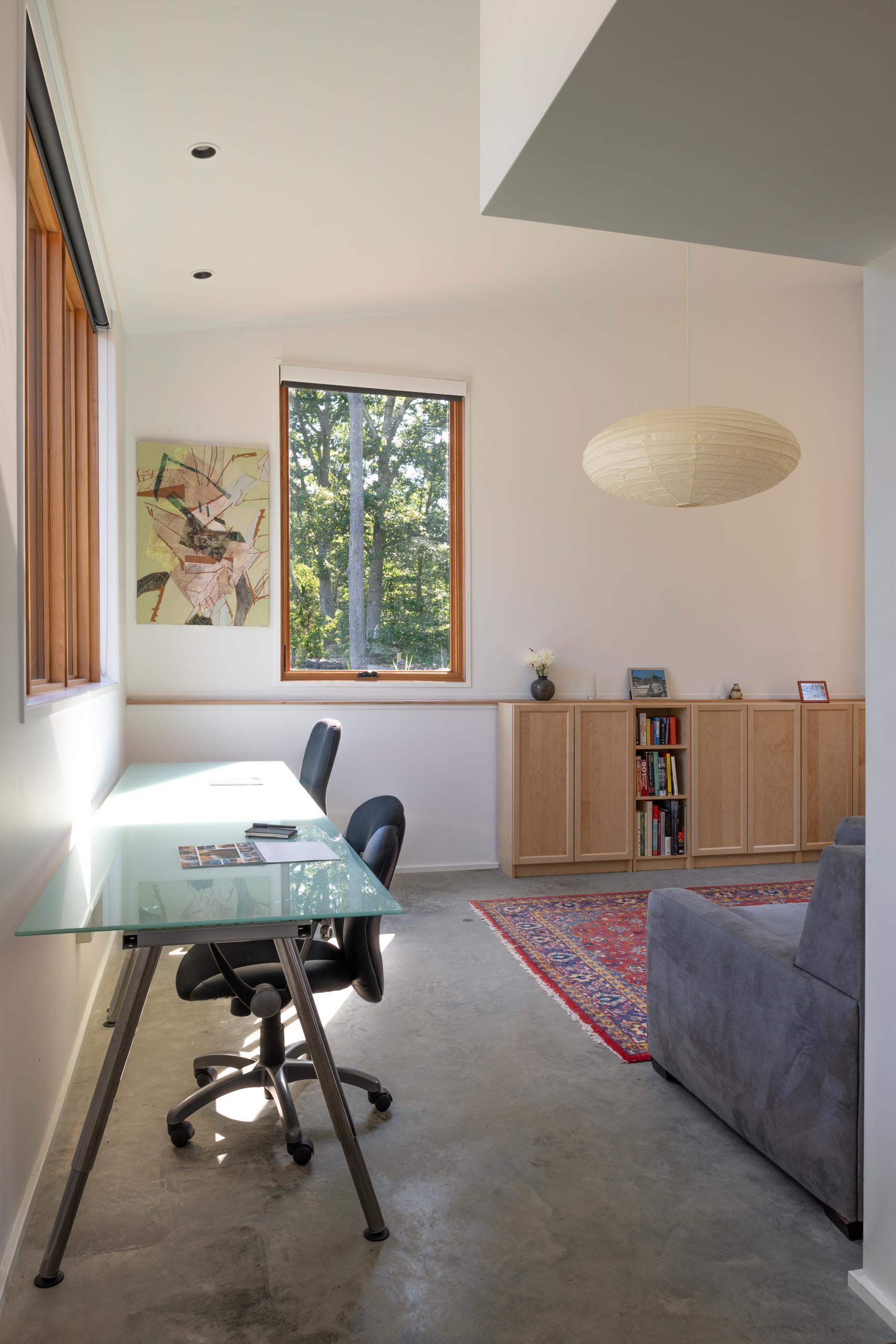 A home office with room for multiple people to work includes a long desk by the window, a couch, and storage cabinets.