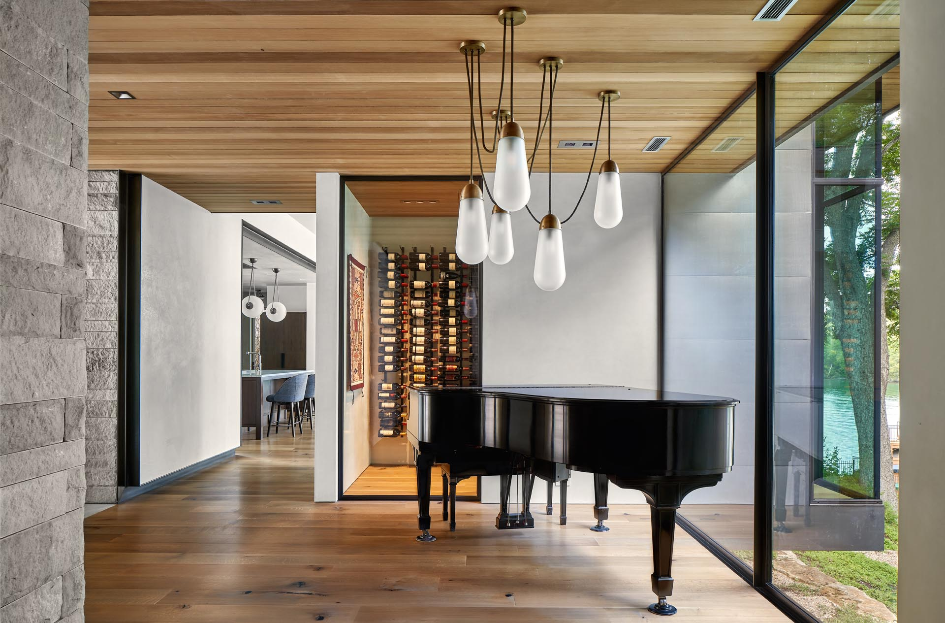 This modern home has a wine cellar and an entryway, which is furnished with a Steinway grand piano and custom Apparatus lighting.
