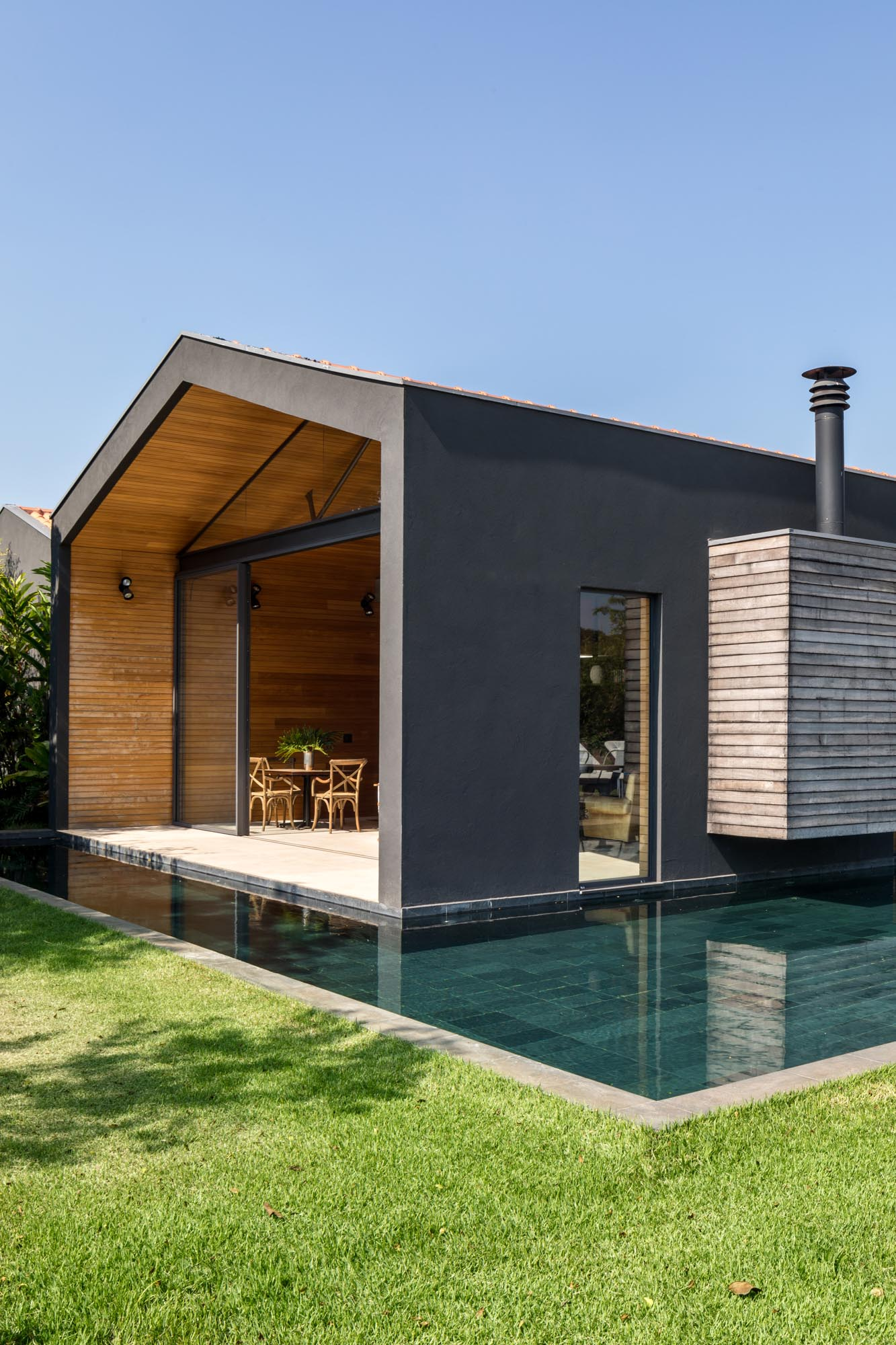 The exterior of this modern home is a black-painted mass, contrasting the surrounding nature, and providing a bold backdrop for the outdoors spaces, like the patio and swimming pool.