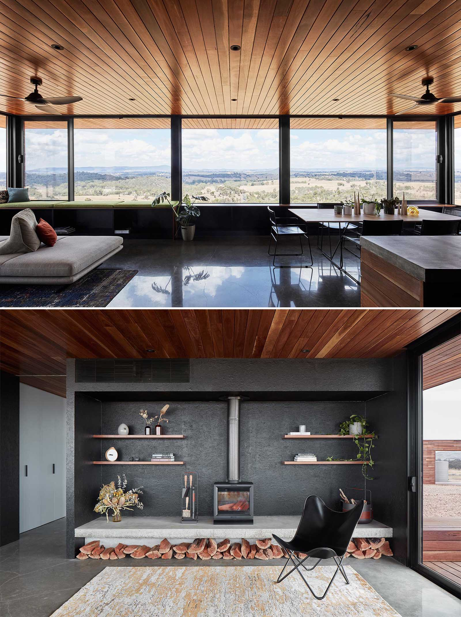 The living space of this small house, has a wood ceiling and large windows, and is open plan with a dining area and kitchen, while the living room includes black accent wall with a fireplace, and a window bench.