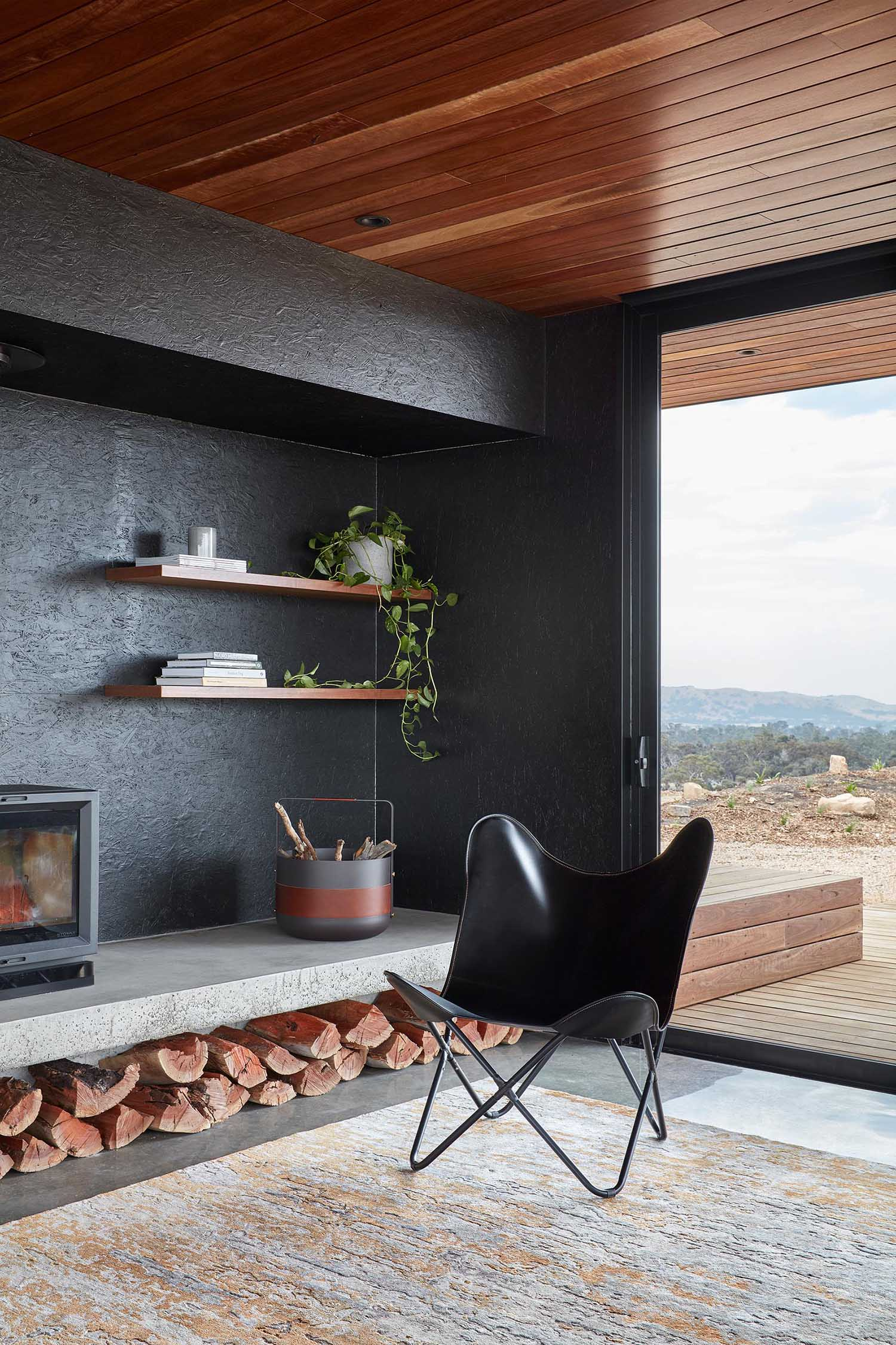 A black accent wall is the backdrop of a fireplace and floating wood shelves.