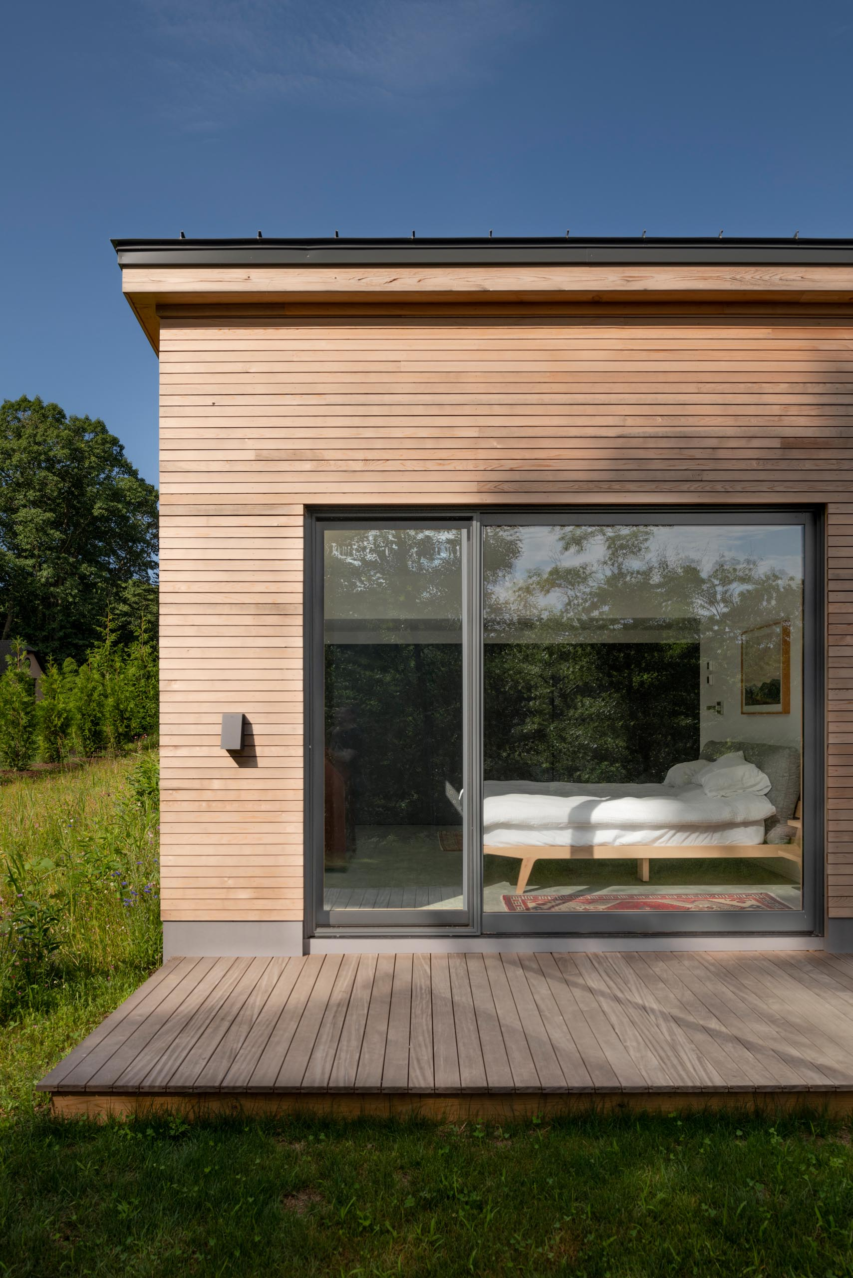A deck wraps around this modern home, while the charcoal-colored window frames provide a contrast to the wood and complement the metal roof and garage door.