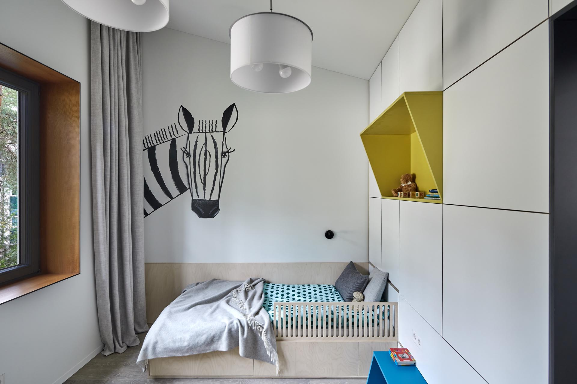 In this modern kid's bedroom, there's a zebra art feature, as well as a colorful yellow shelf and a green desk surrounded by storage.