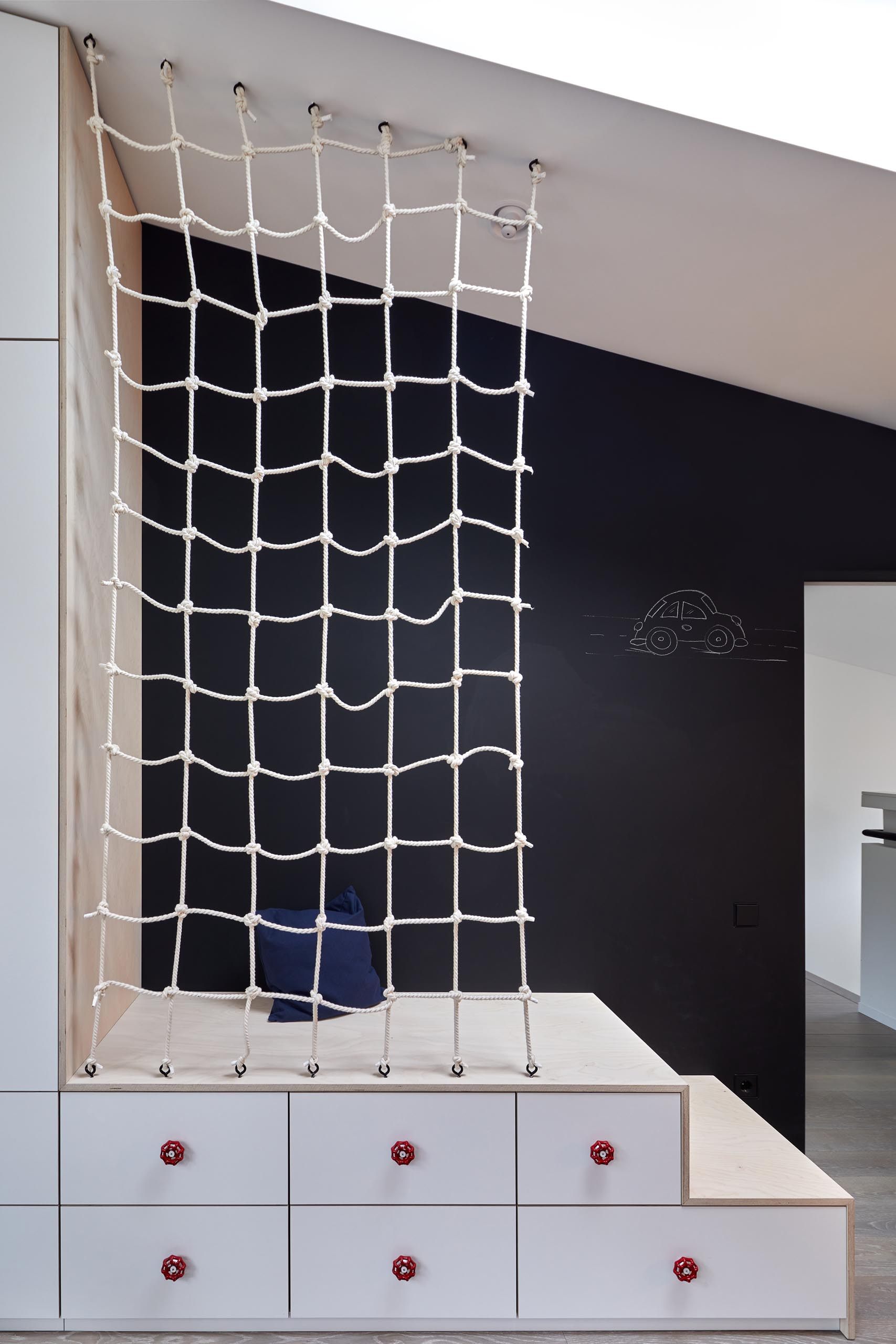 In this modern kid's bedroom, there's a chalkboard wall, built-in stepped storage, and a net accent.