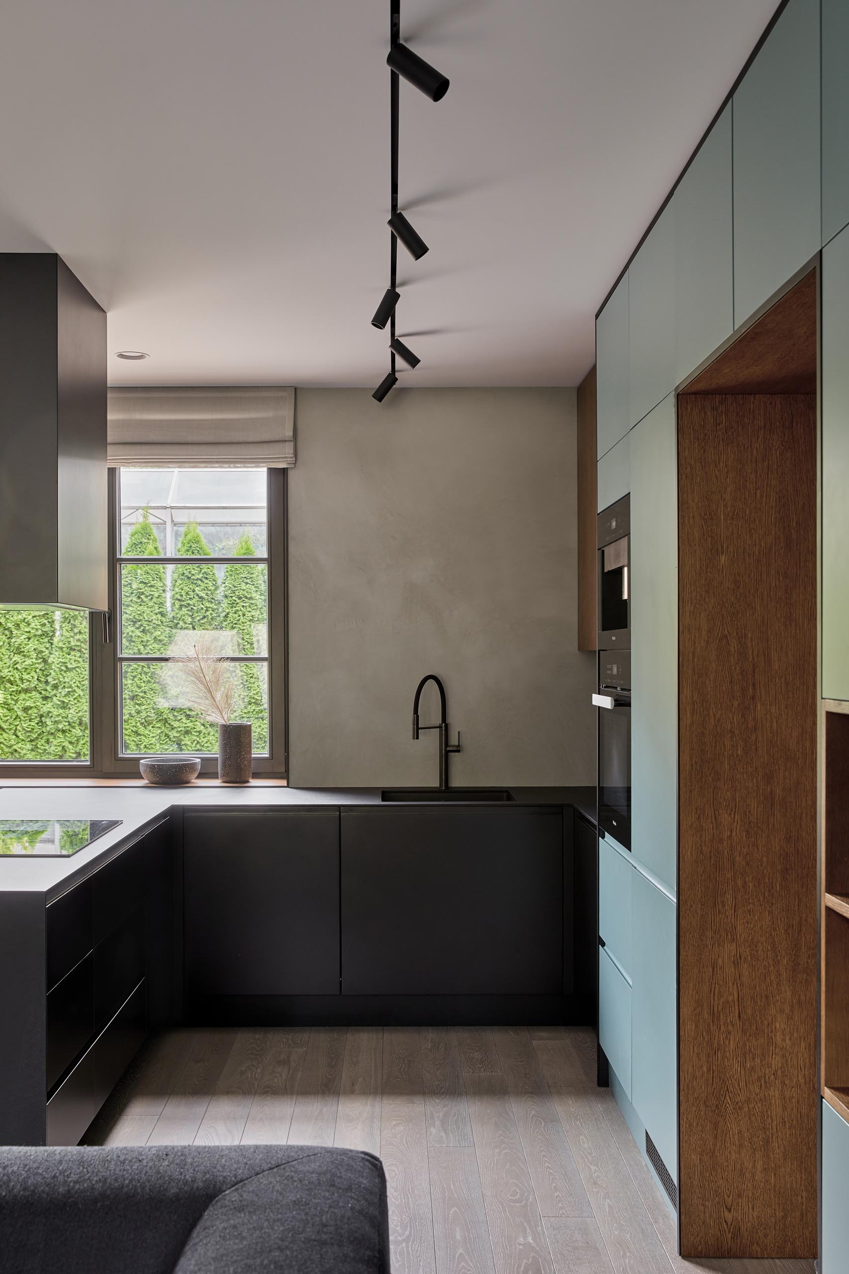 An open plan room living room, dining room, and kitchen, has a muted mint green wall that's filled with minimalist cabinetry and open wood shelving. The cabinets continue through the kitchen where they meet black cabinets and a matching countertop.