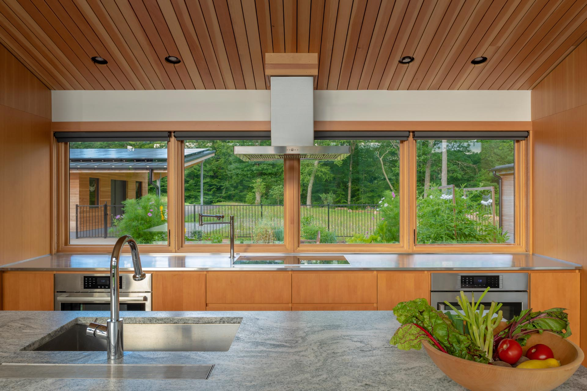 The kitchen has a large island with an undermount stainless steel sink, while windows look out to a courtyard and the workshop.