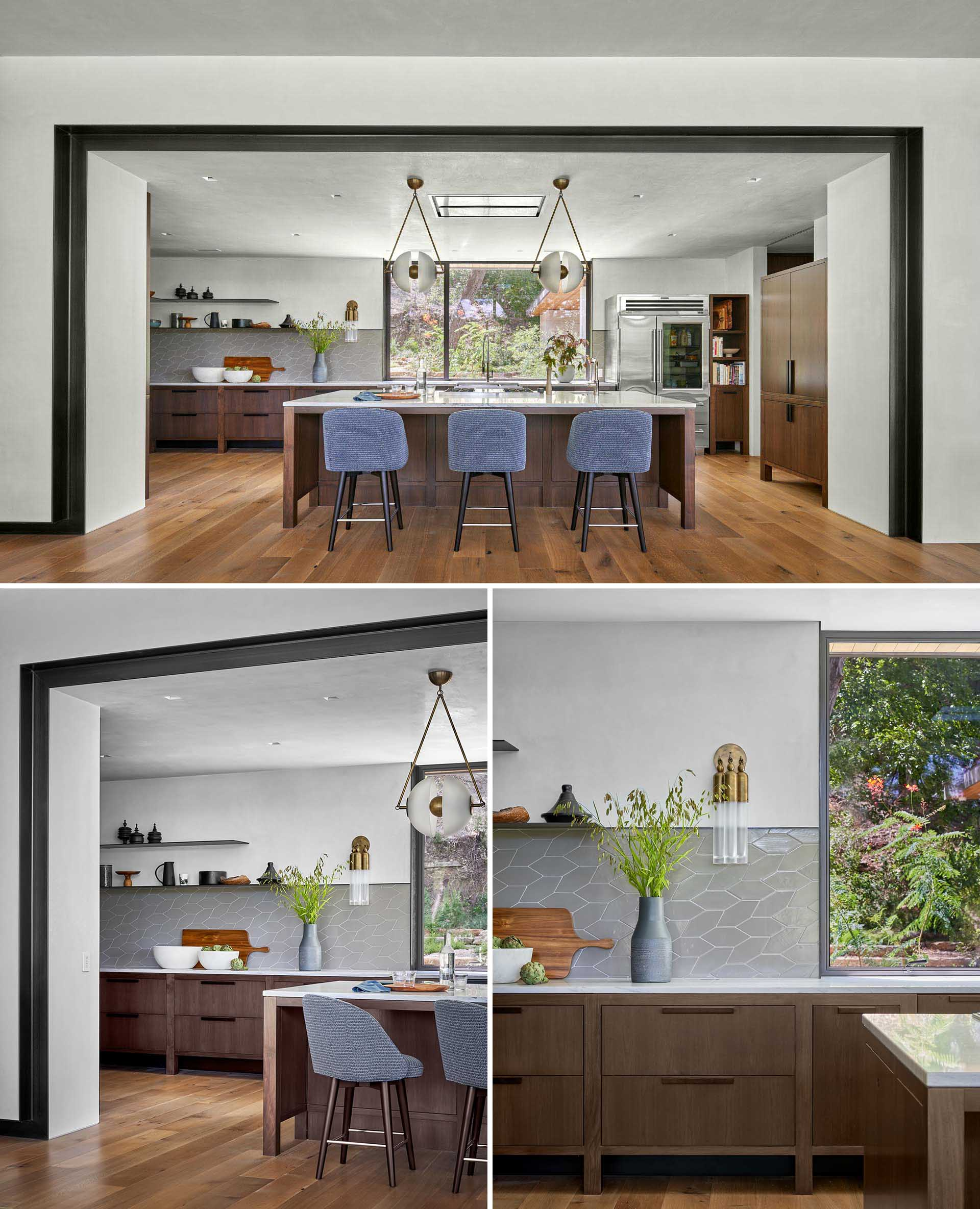 This modern kitchen features cabinets on wooden legs that create a physical and visual space between the floor and cabinets. A glass front refrigerator adds to the design of the kitchen, while a custom kitchen armoire stores coffee making equipment.