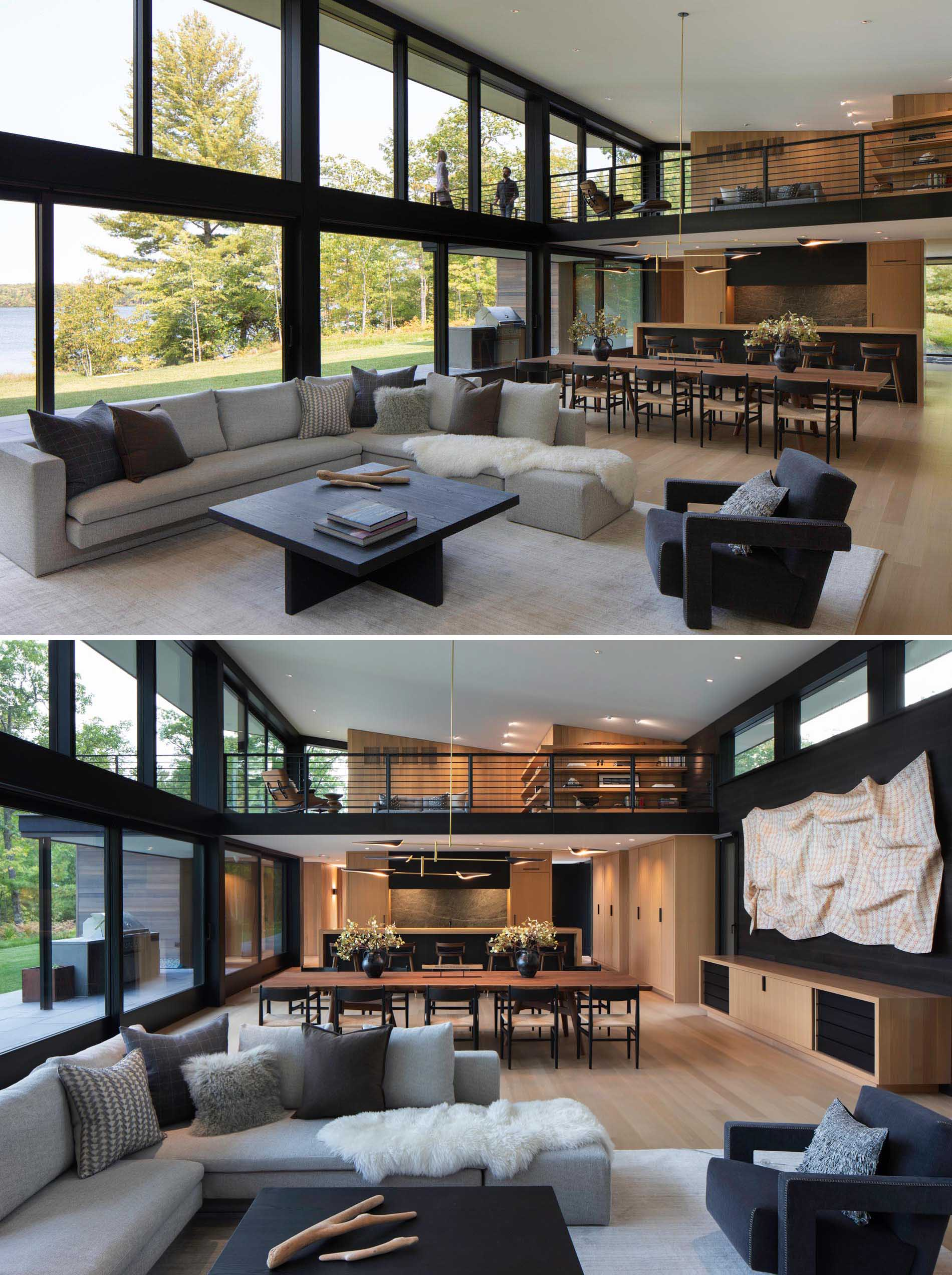 This living room, furnished with an L-shaped gray couch, has a wall of windows and glass doors, with the doors providing access to the patio and outdoor kitchen. There's also a view of the loft which opens up to a balcony.