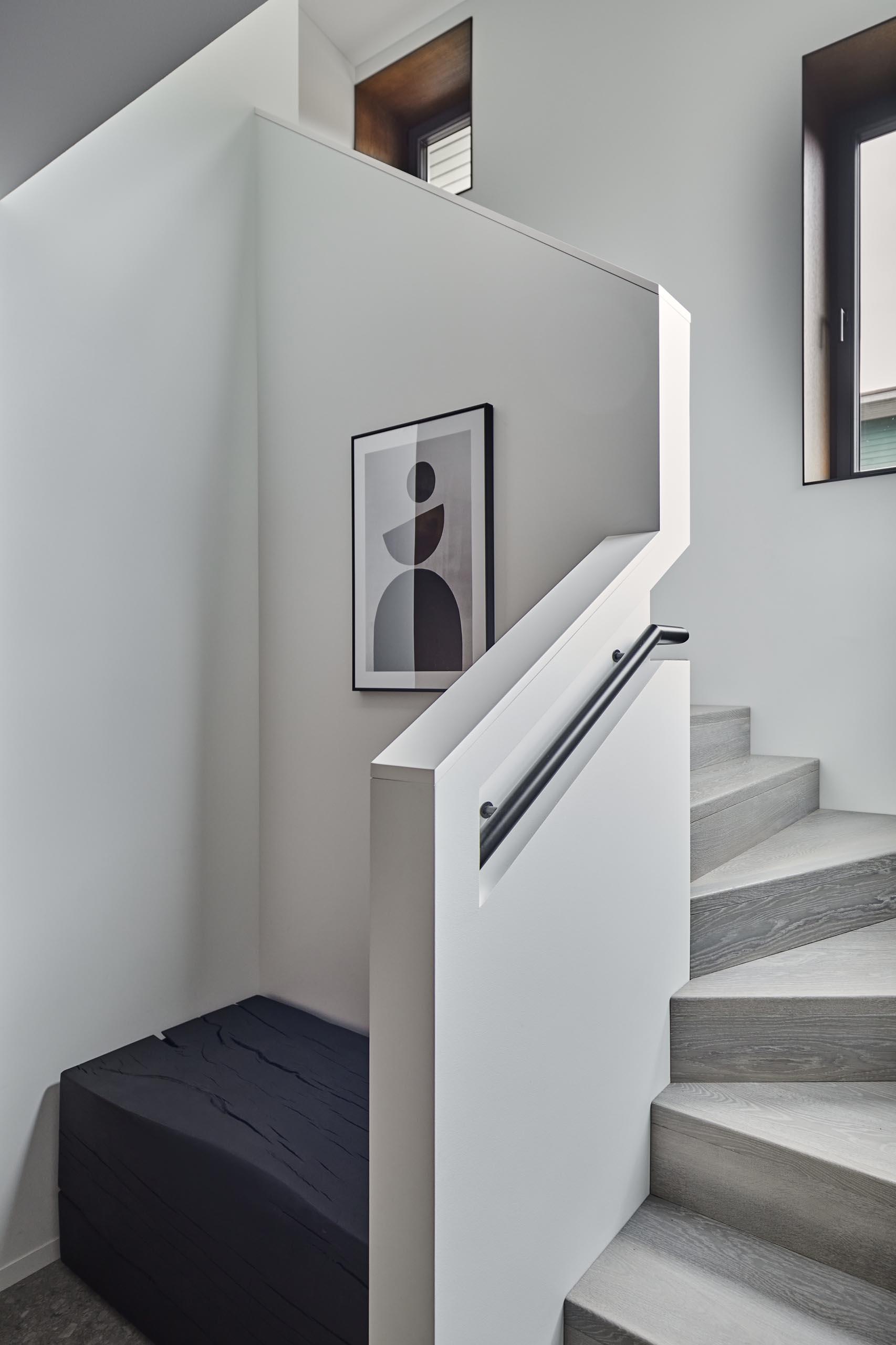 This modern entryway includes wood cabinets and a burnt wood bench. Stairs with a built-in handrail lead to the upstairs.