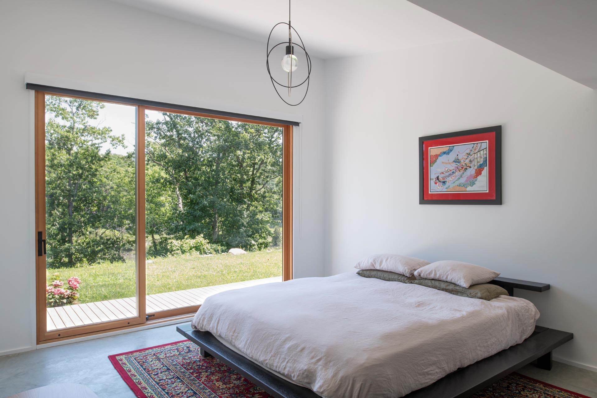 A minimalist bedroom with white walls, modern furniture, and a large window that looks out onto the marshland.