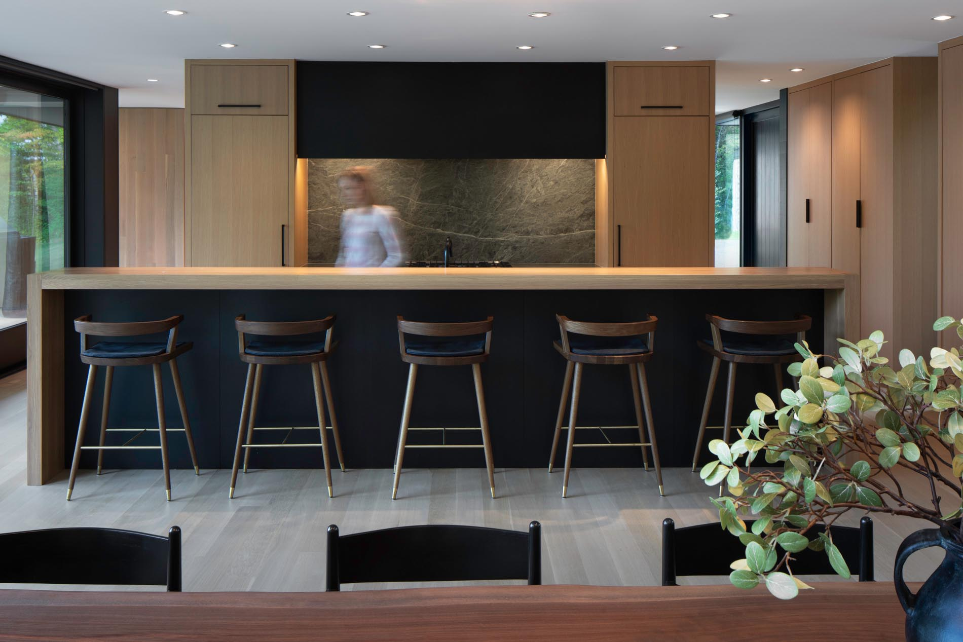The design of the kitchen includes rift-sawn white oak cabinetry, a custom black metal hood, stone backsplash, and an island that's long enough to seat five.