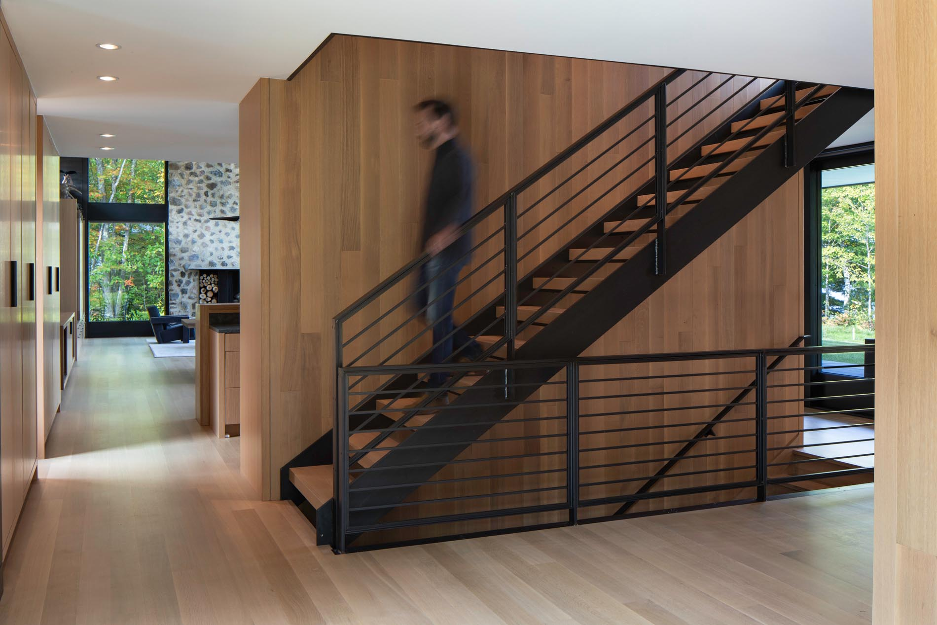 Metal railings with white oak treads match the wood used in the kitchen, and lead to the loft and the lower level of the home.