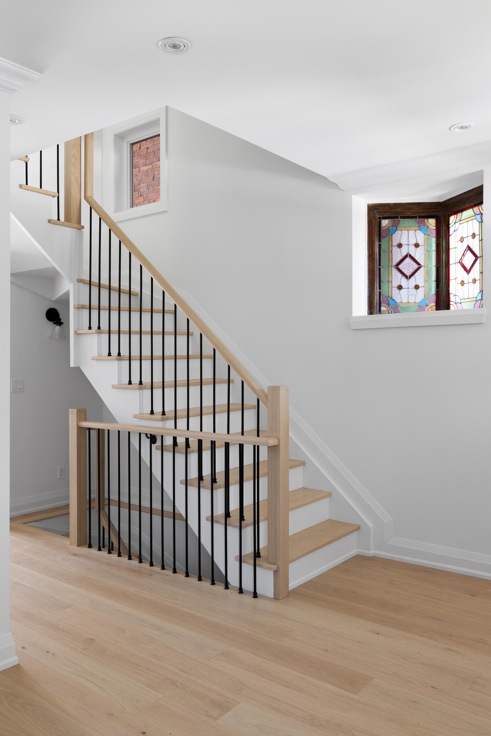 This contemporary staircase provides views of original stained glass windows, that were kept as a nod to the former design of the house.