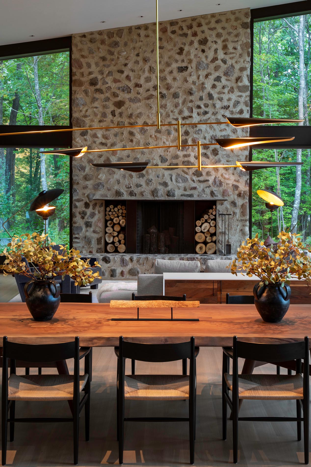 A custom wood dining table by Michael Dreeben and a sculptural David Weeks chandelier separate the living room from the kitchen. The dining area also provides a view of the fireplace that showcases hand-troweled masonry and field stone.