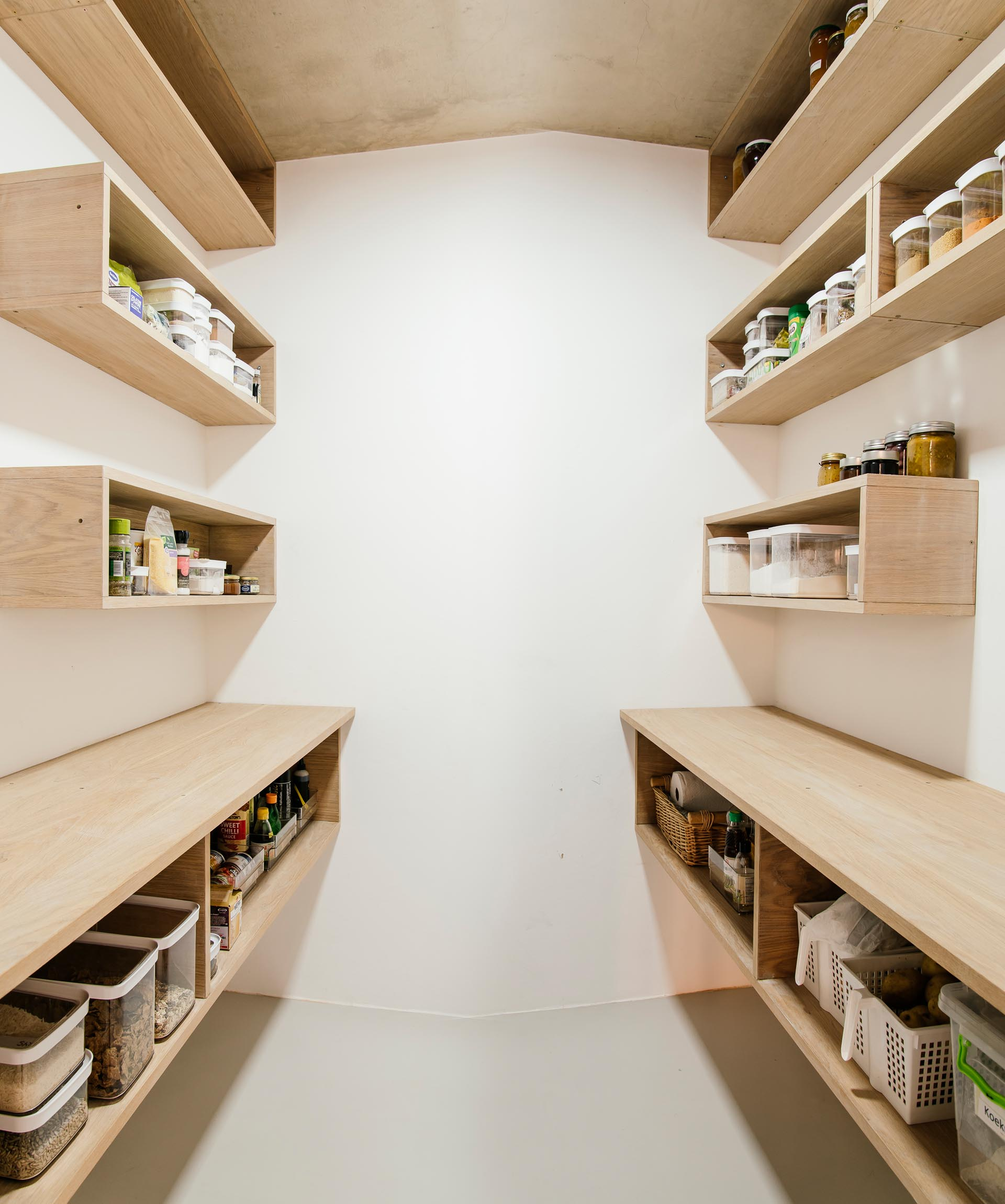 A modern pantry with wood shelves.