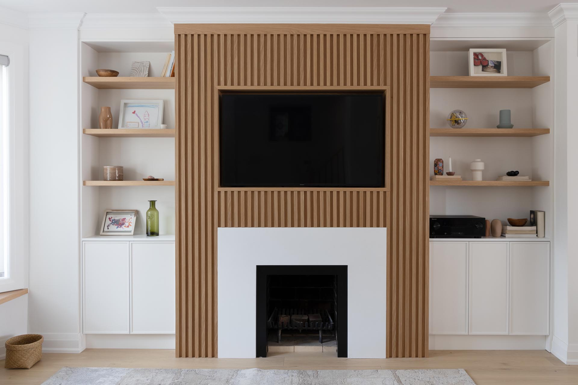 This living room wall has a Scandinavian-inspired design that includes a wood slatted wall that draws the eye, adds a sense of depth, and surrounds the television and fireplace.