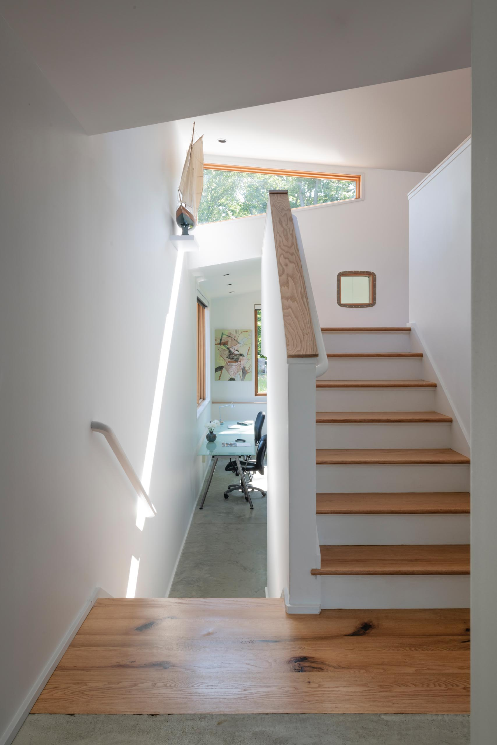 White stairs with wood treads lead to a lofted area in this modern home.