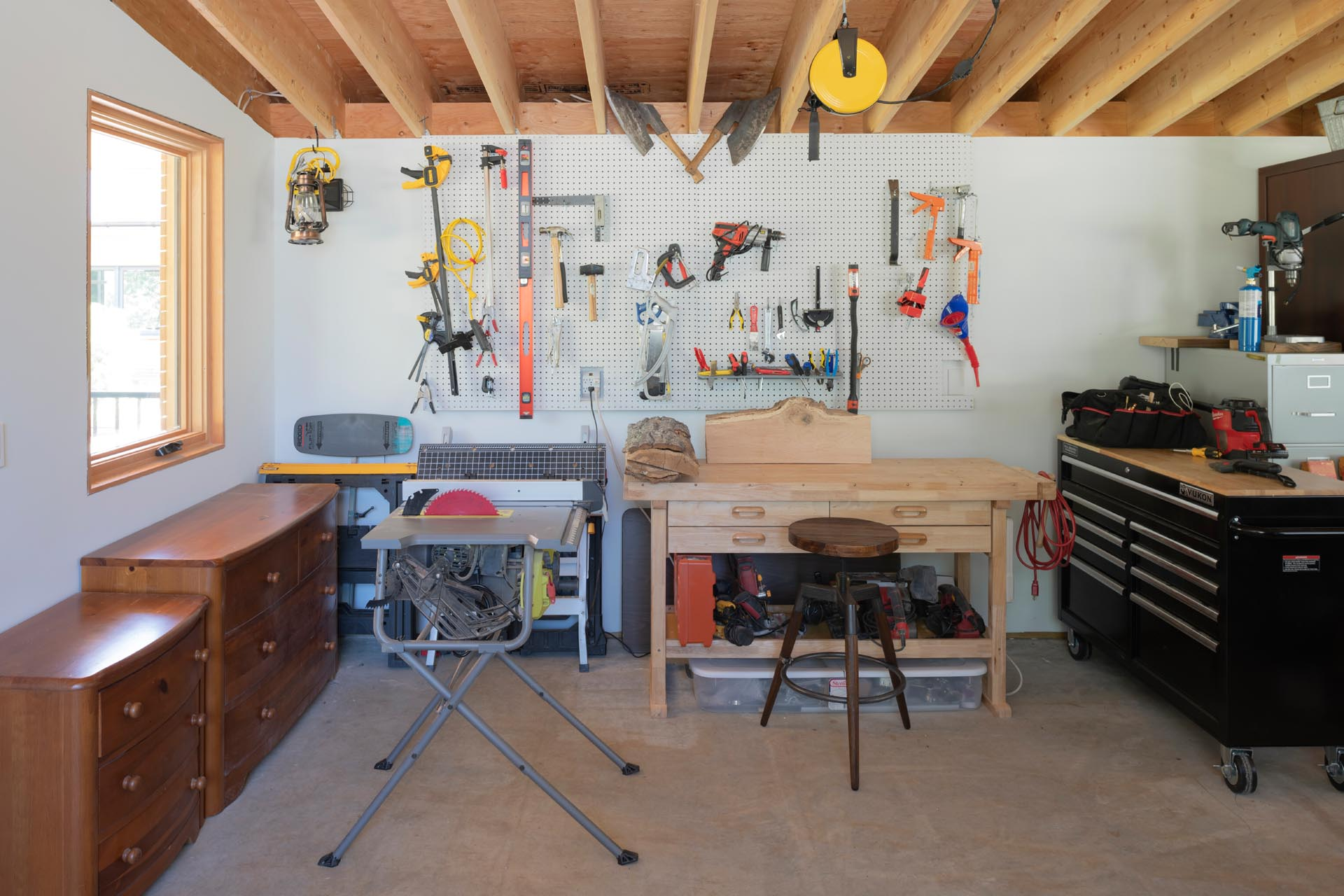 A large garden and carpentry workshop has room for a workbench, furniture and tool storage, and an indoor potting area with a large sink.