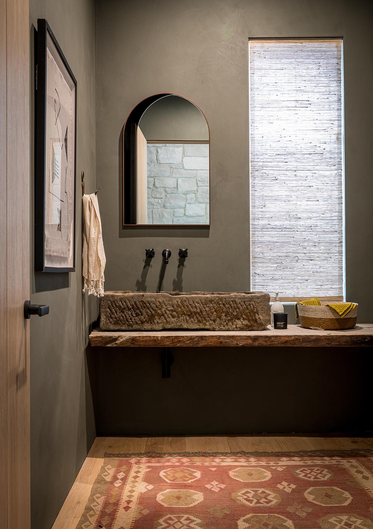 A contemporary farmhouse inspired bathroom with stone sink and live edge wood vanity.