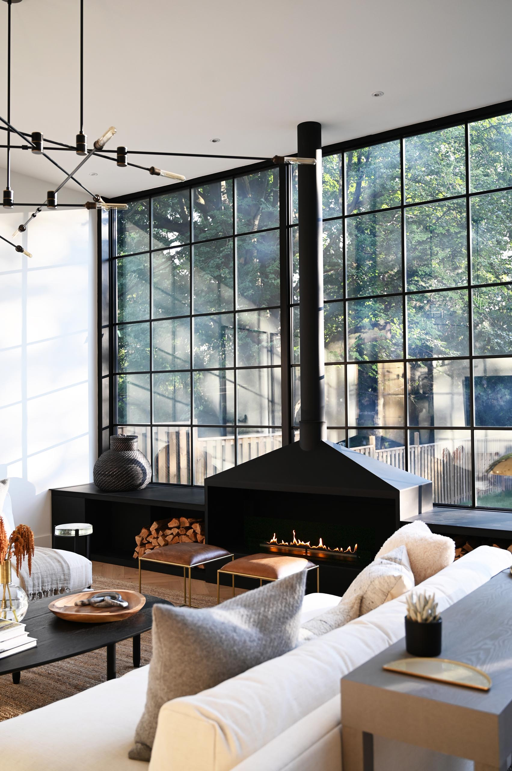The expansive wall-to-wall black-framed windows and door frames complement the interior of the living room, that showcases a matte black fireplace and window bench. Also included in the design of the window bench is firewood storage.