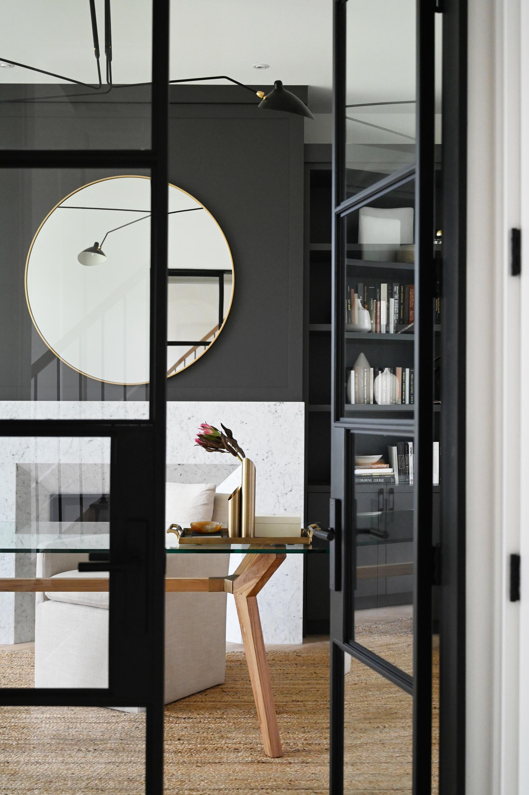 A modern home office has a black accent wall that provides a backdrop for the fireplace, while built-in shelving and cabinets add a storage element.