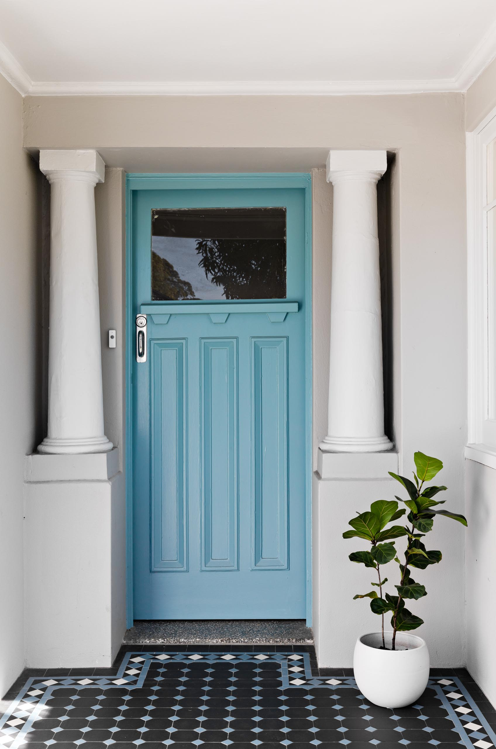 A renovated home with a brick blue front door.