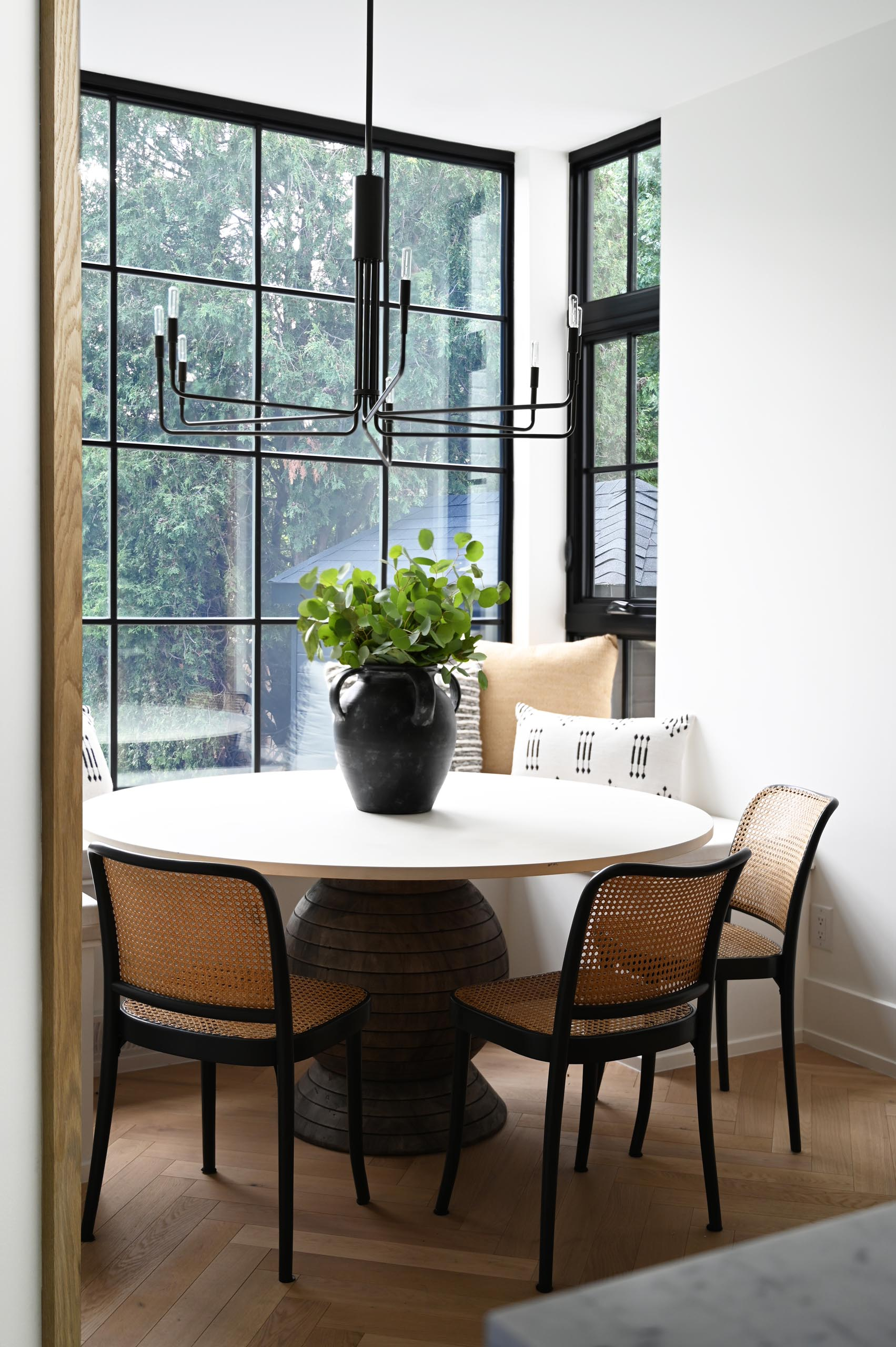 In this modern breakfast nook, the black window frames match the pendant light and the chair frames.