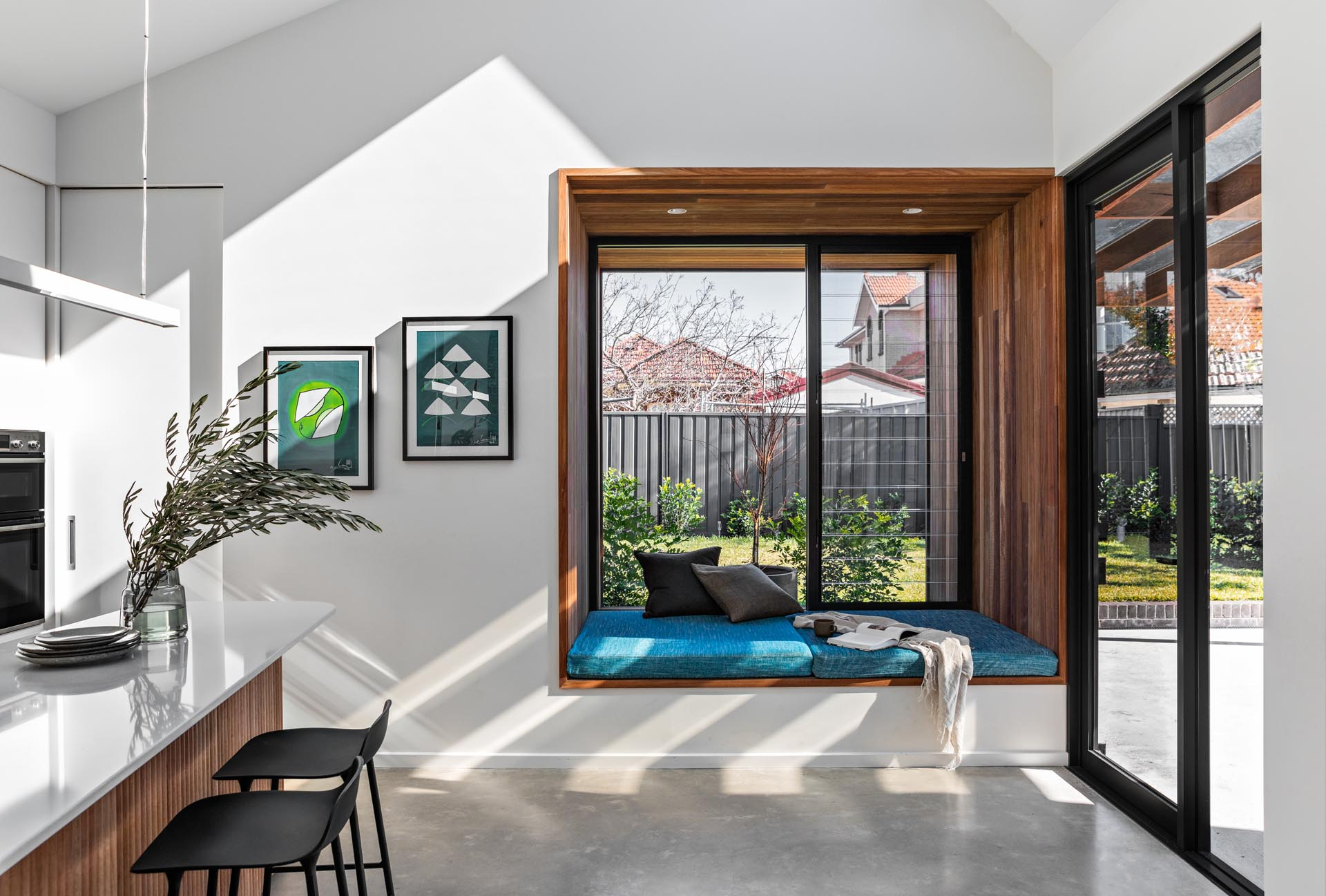 A large square timber-lined window box seat with blue upholstered cushion, that extends the view out to the garden.