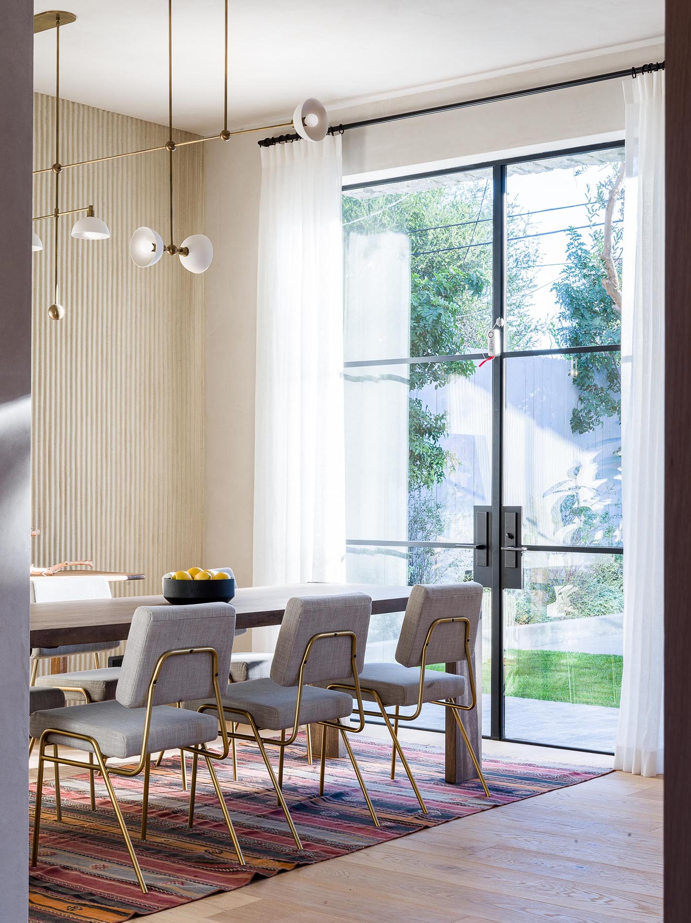 This modern formal dining area showcases a statement plaster wall, while black-framed glass doors open to the backyard.