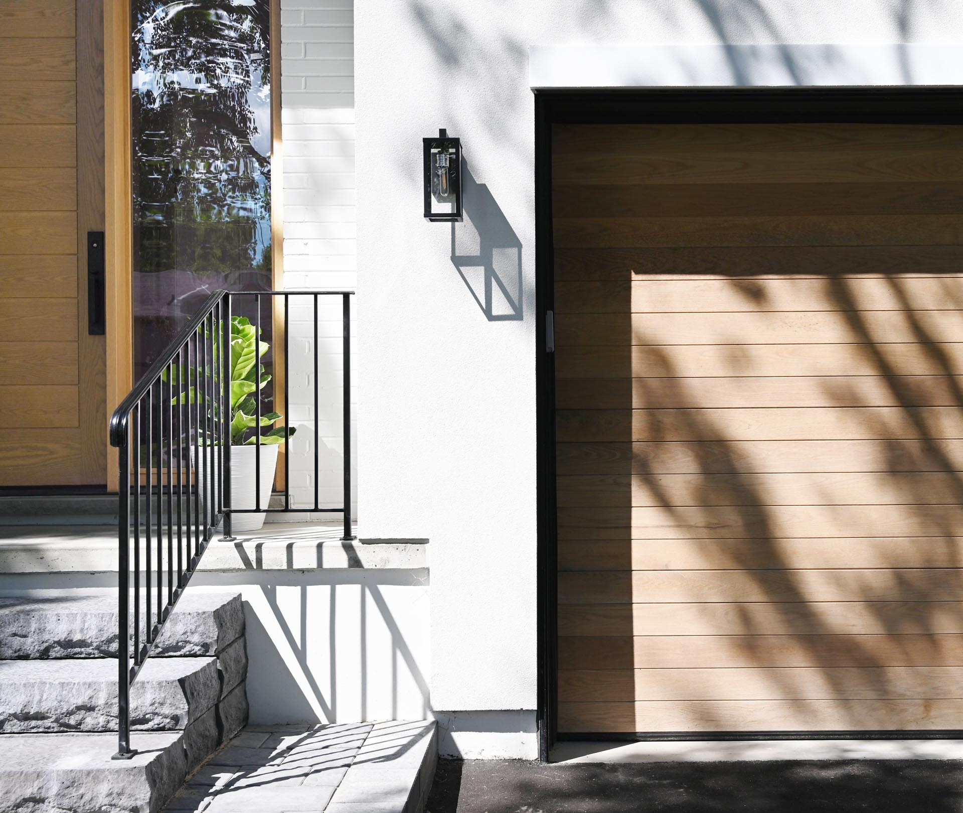 This contemporary home was inspired by farmhouse living, with the white exterior accented by natural white oak wood to add a warm welcome and a hint at what lies beyond.