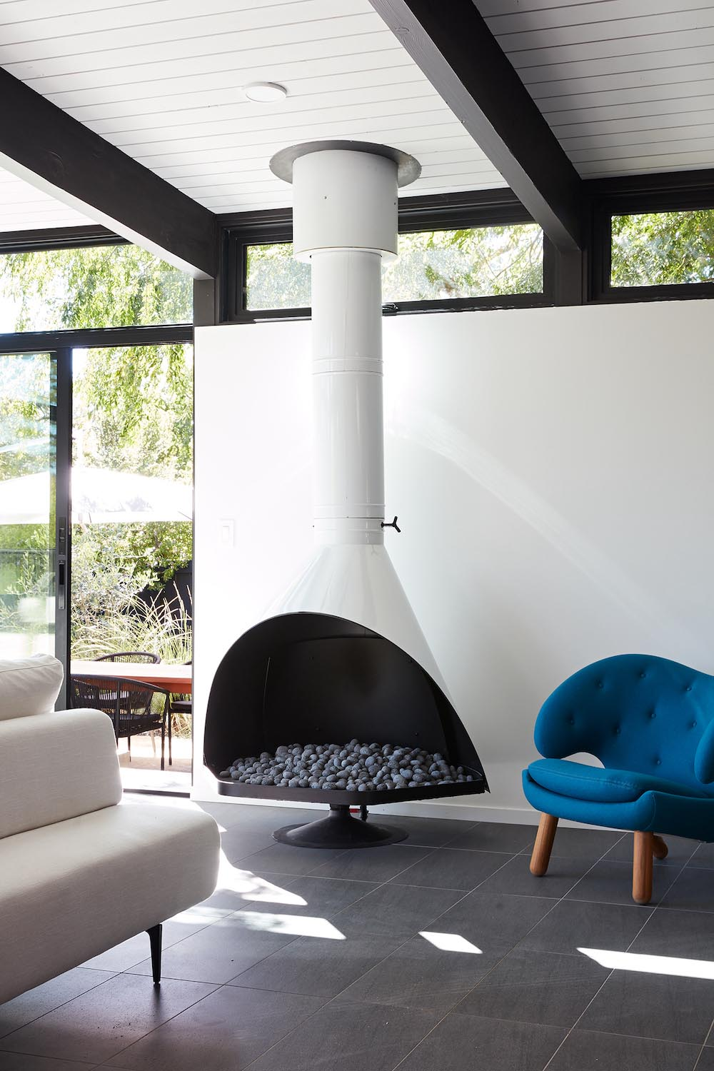 A remodeled living room with a Malm fireplace, black accents, and white walls.