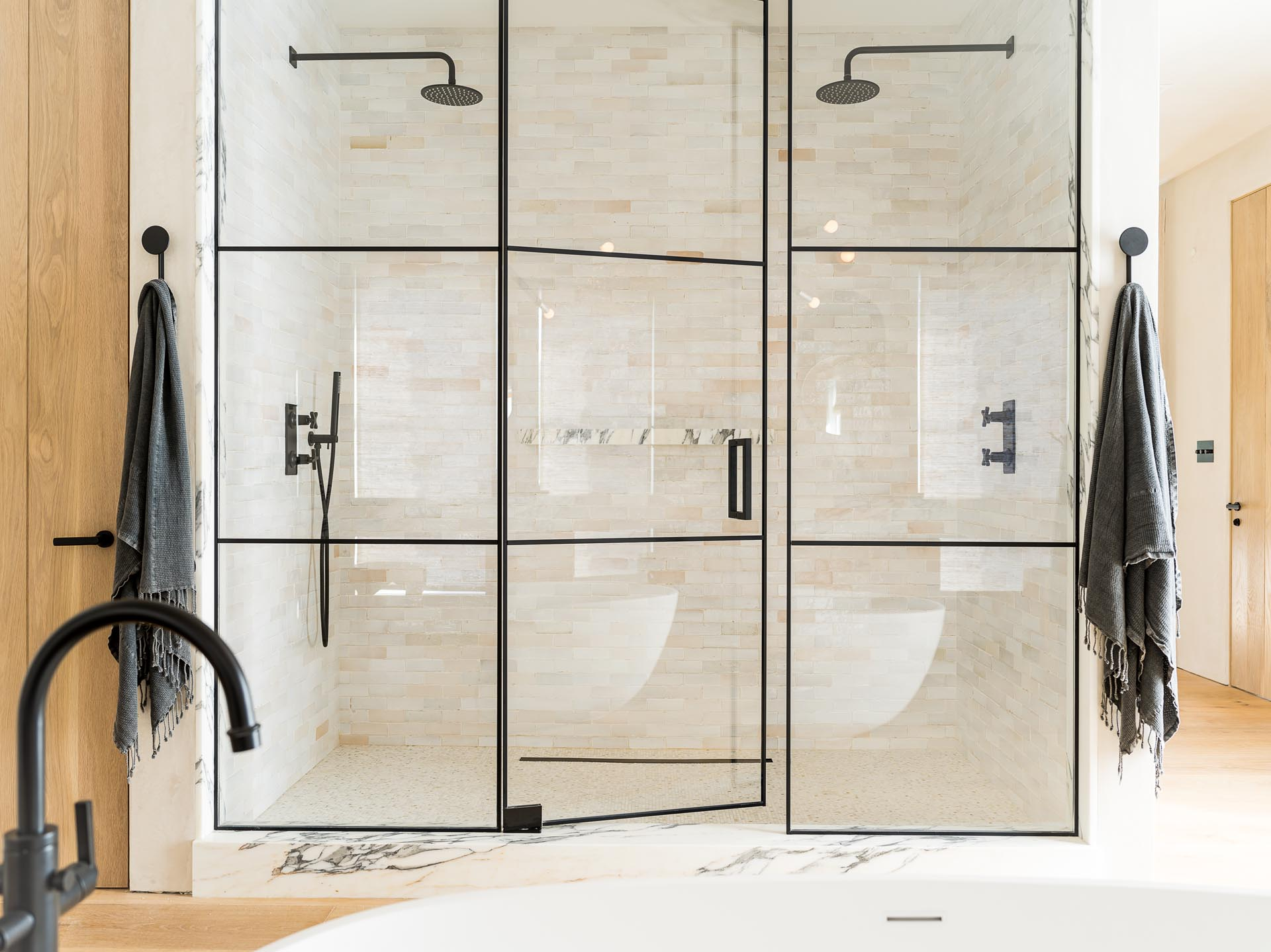 A glass enclosed two person shower with black frames and hardware.