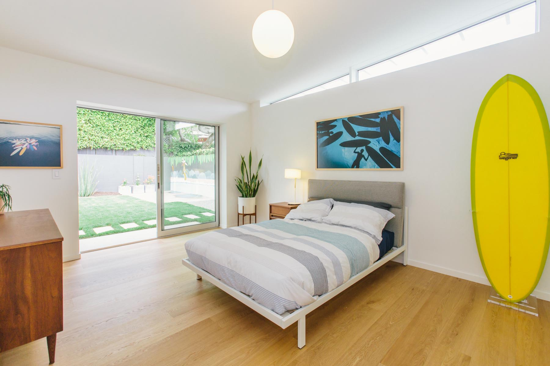 A mid-century modern inspired bedroom has clerestory windows and a sliding door that opens to the yard.