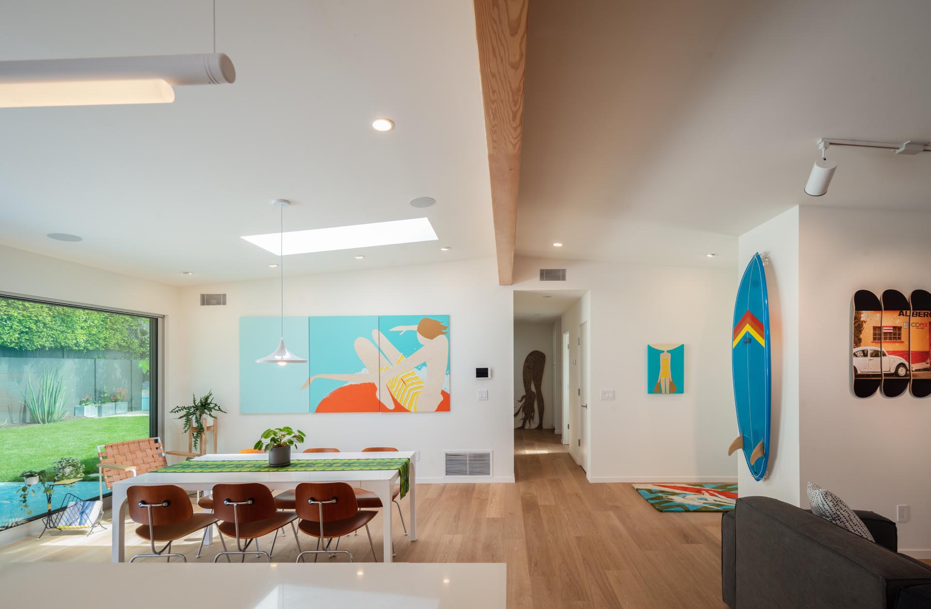 This modern open plan dining area has been furnished with a white dining table and a colorful 3-panel art piece on the wall. A skylight adds natural light to the space.