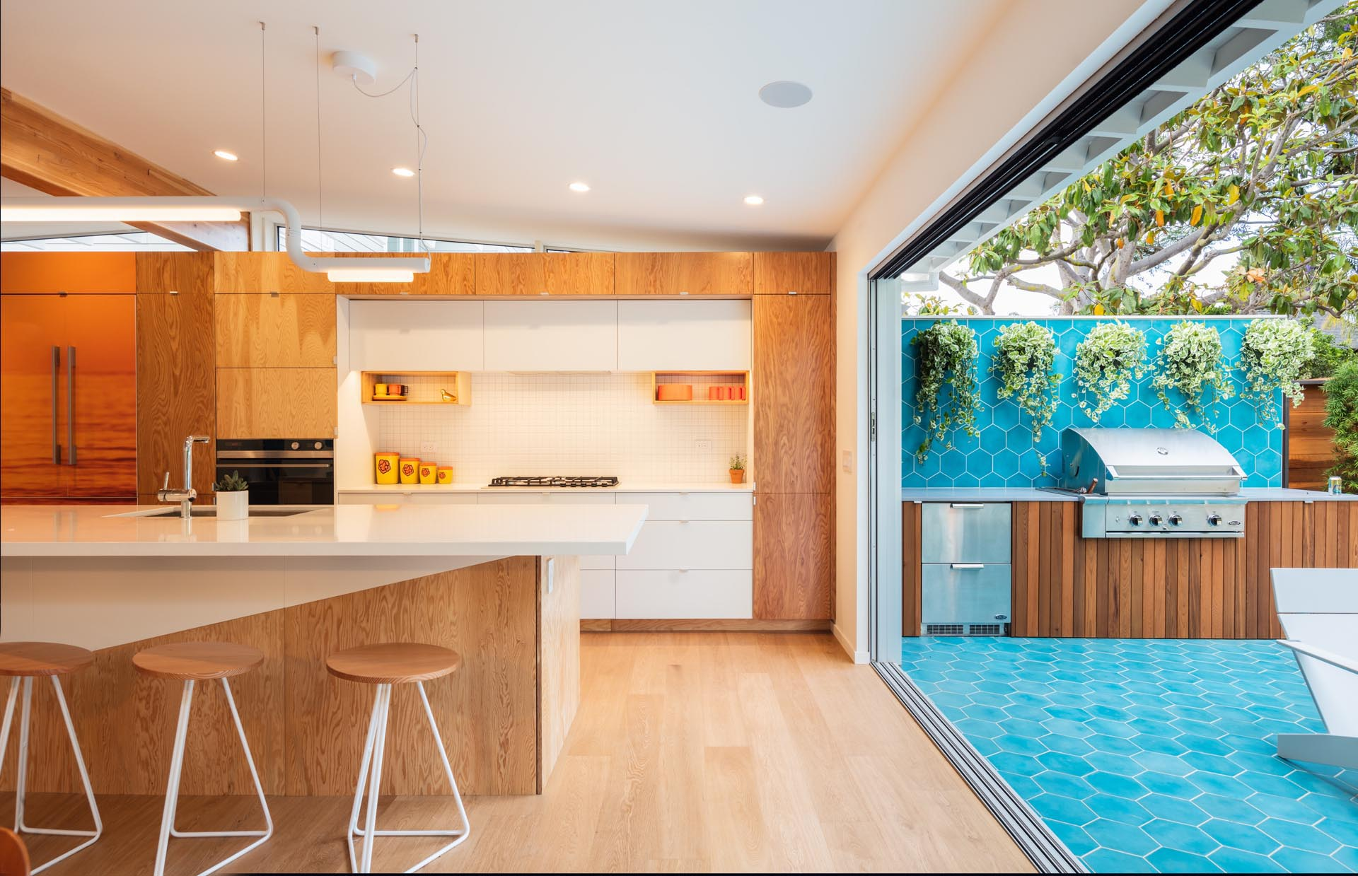 A large sliding door opens to the outdoor kitchen and yard.