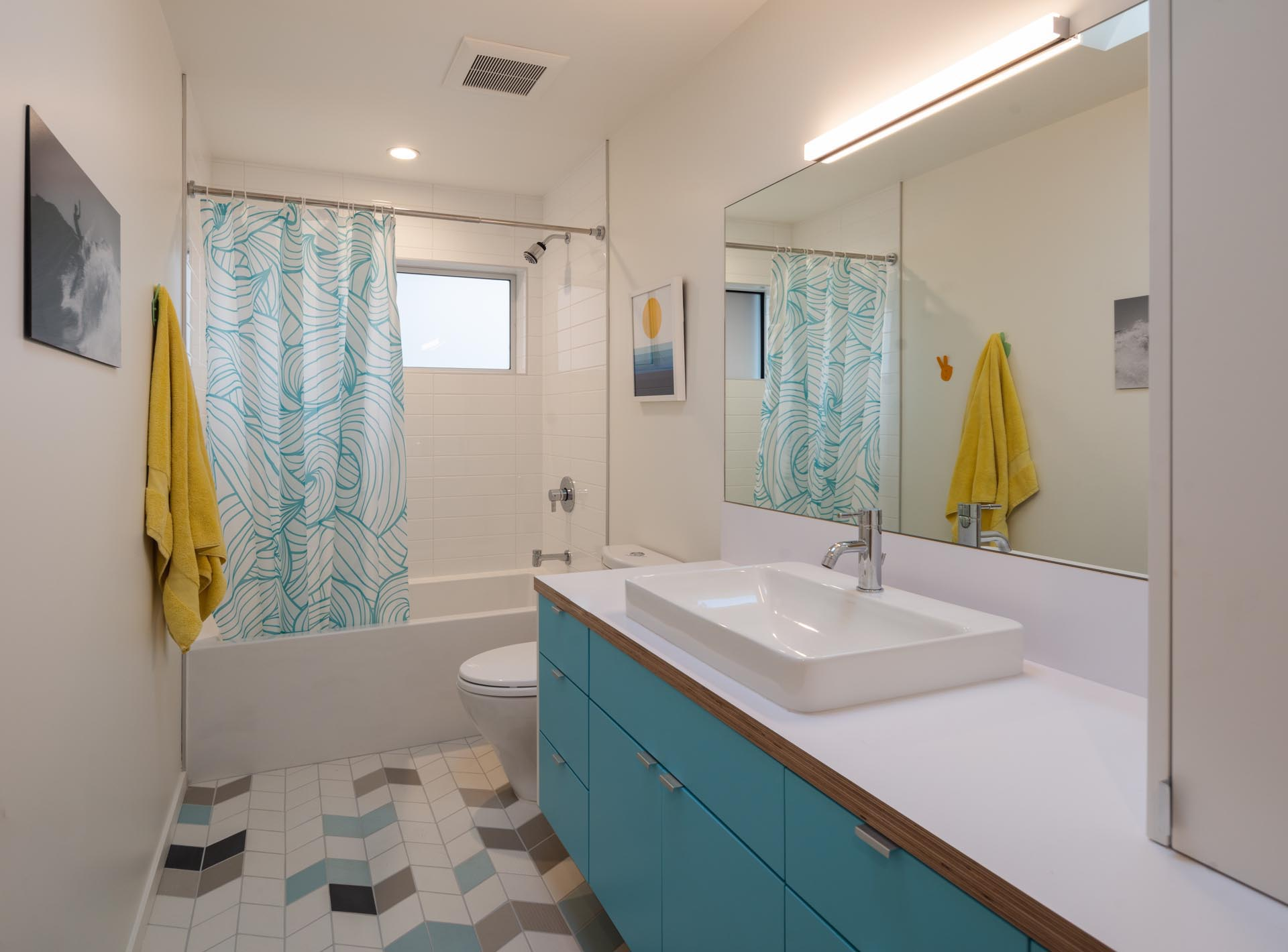 In this bathroom, a bright blue vanity is topped with a white countertop, while the chevron floor tiles feature a few different colors adding interest to the room.