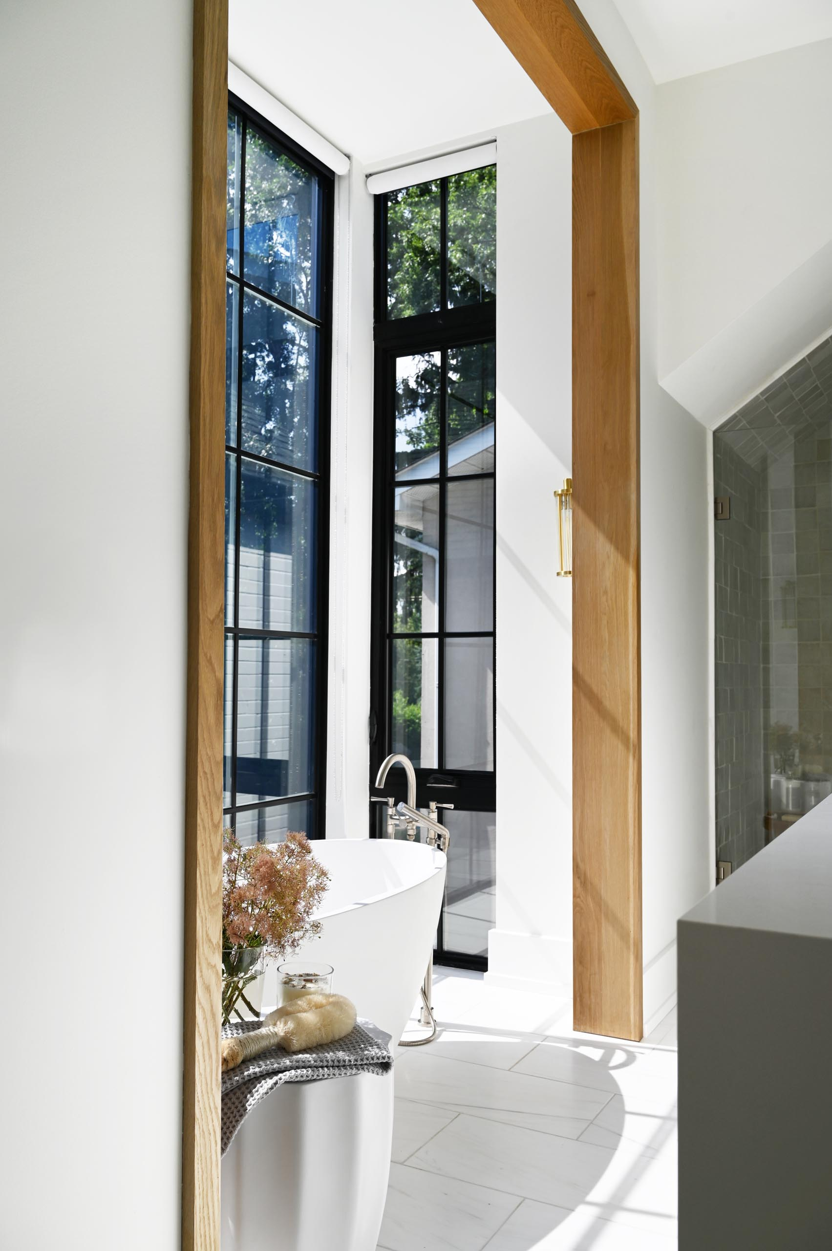 This modern white marbled spa-like bathroom includes a windowed alcove for the freestanding tub, metallic hardware, and wood accents.