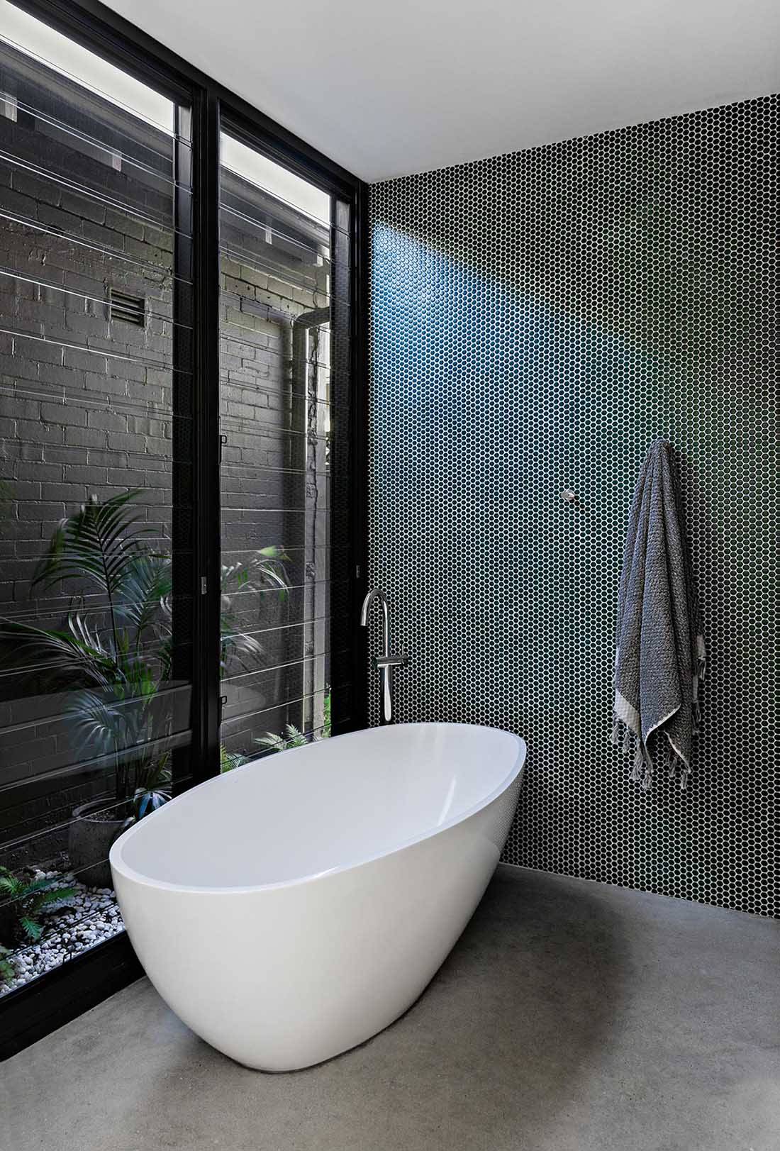 A modern bathroom with a green penny tile accent wall, freestanding bathtub, louvre windows, and concrete flooring.