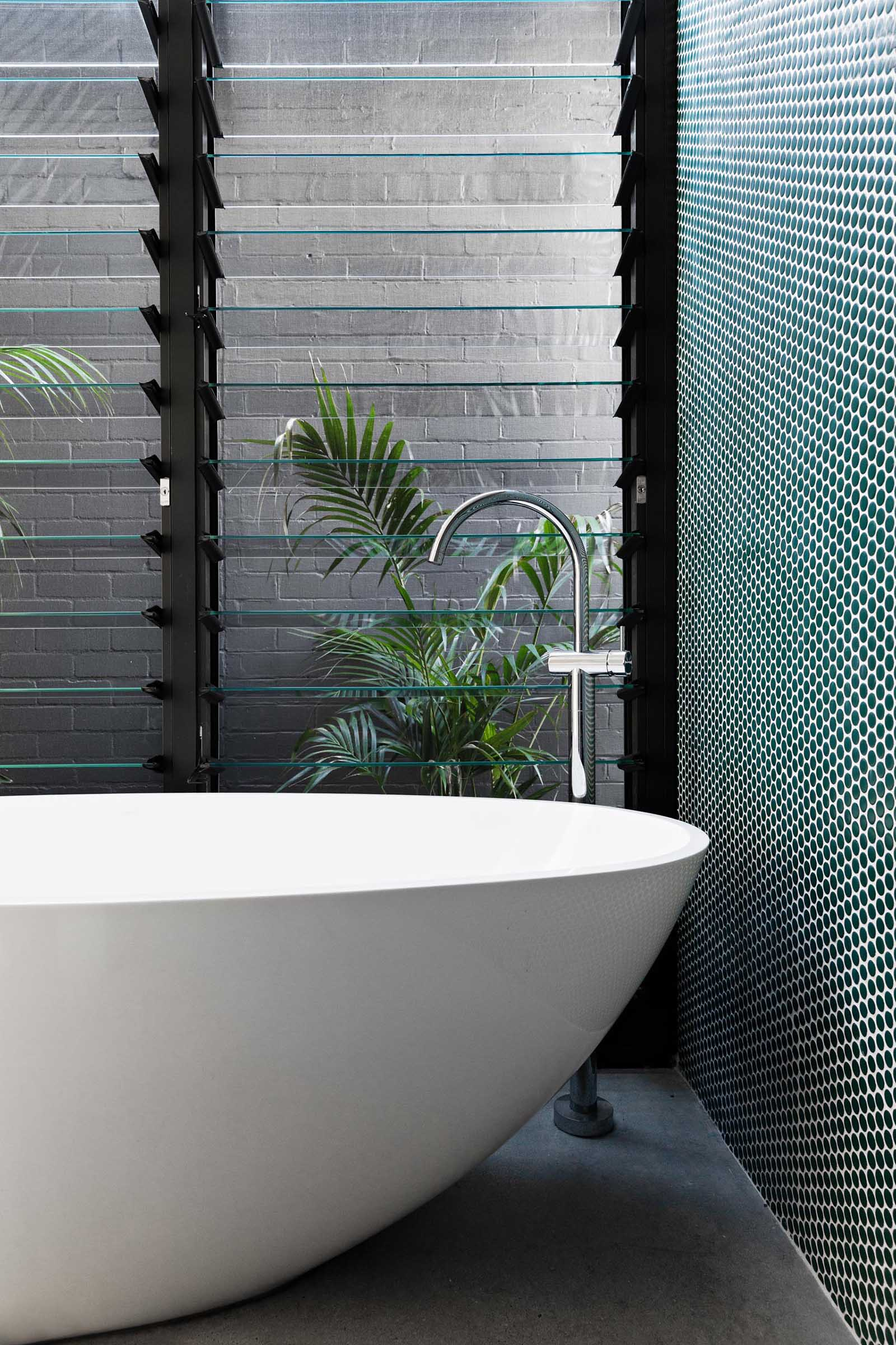 A modern bathroom with green penny tile accent wall, freestanding bathtub, and louvre windows.