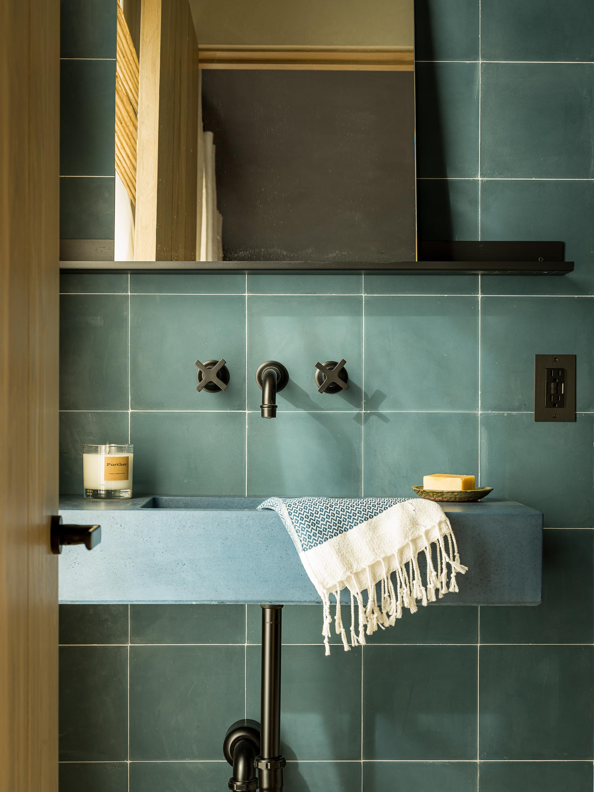 A contemporary blue-green bathroom with square tiles, a blue sink, and black hardware.