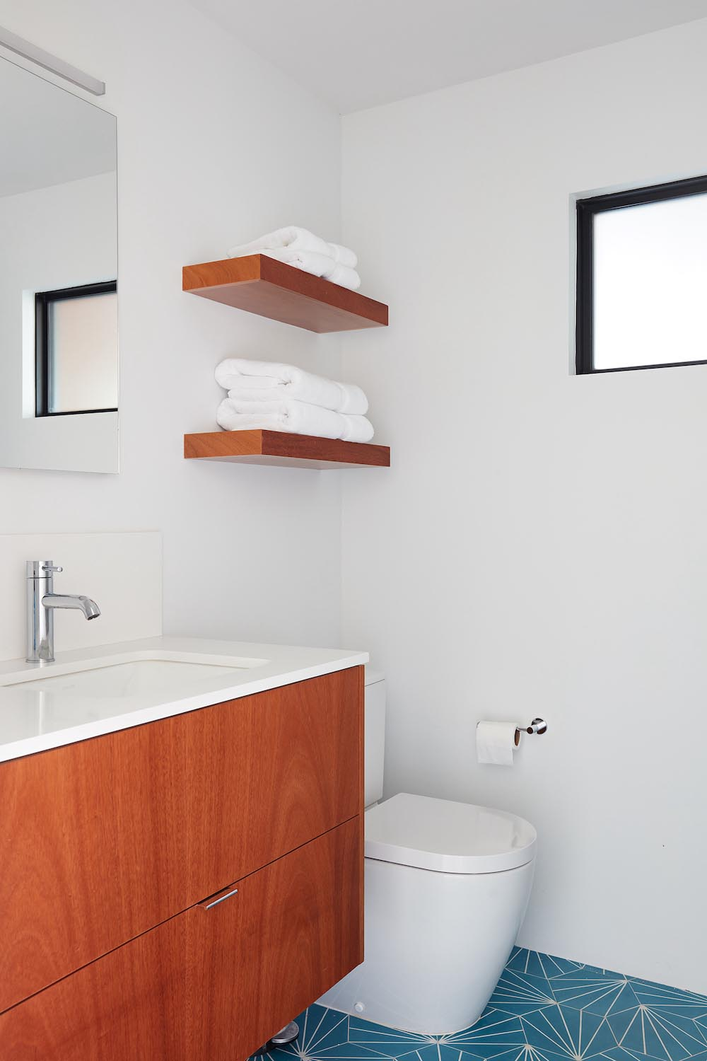 A modern white bathroom with blue starburst tiles and a wood vanity.