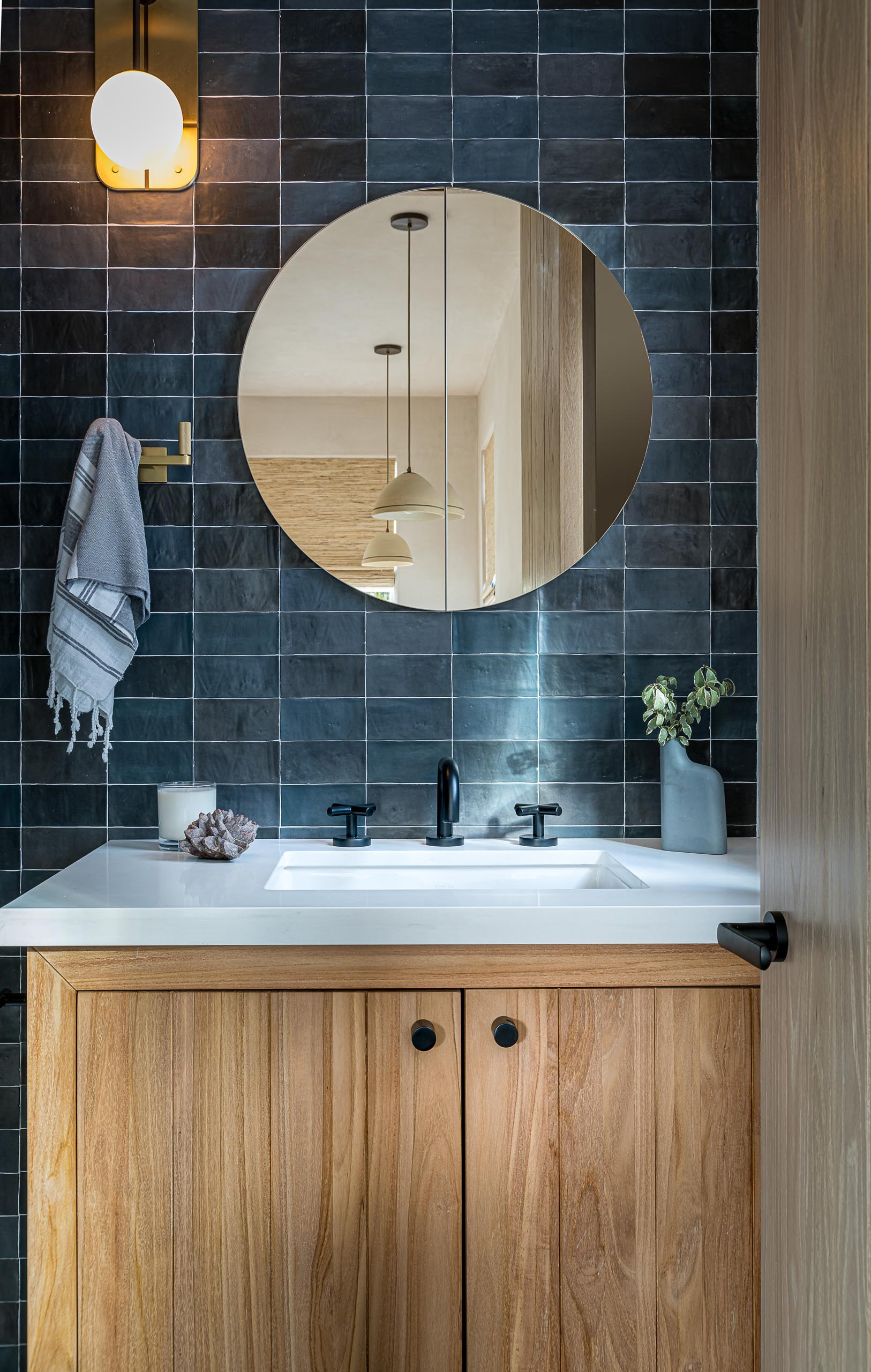 A contemporary bathroom with textured blue tiles, a wood vanity with white sink and countertop, and a round mirror.