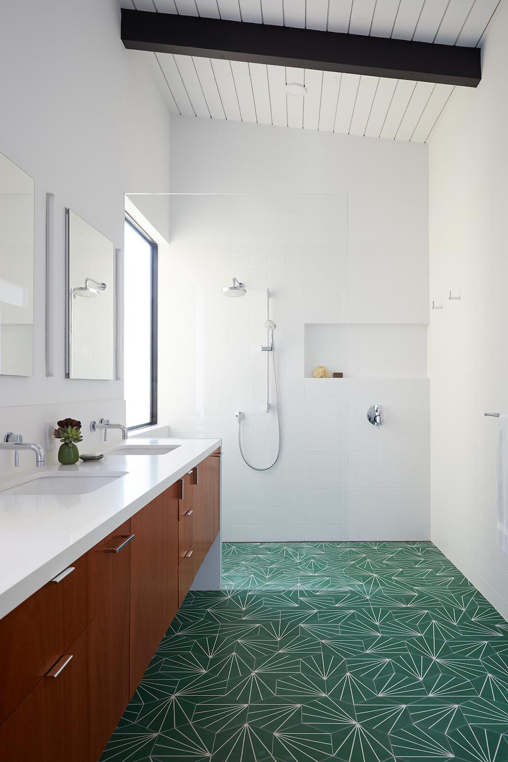 A modern white bathroom with green starburst tiles and a wood vanity.