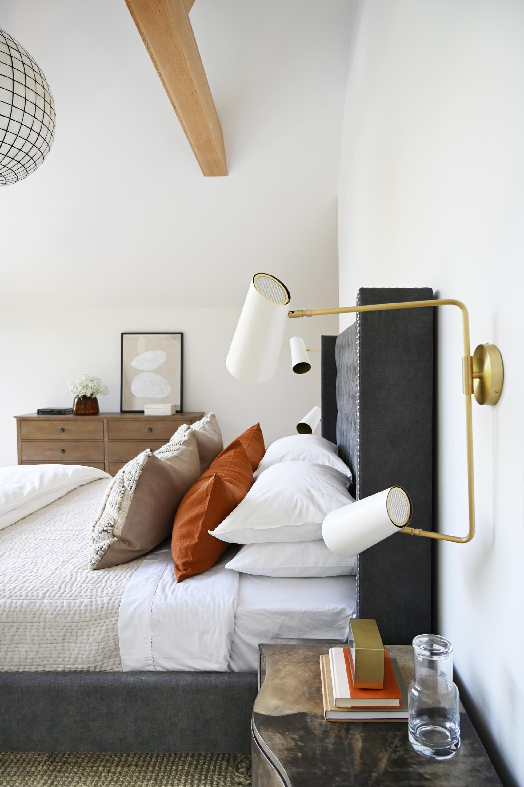 Featuring a cathedral ceiling with exposed beams and layers of neutral soft textures and furnishings, this primary bedroom is designed as a cozy nest overlooking the lush green yard.